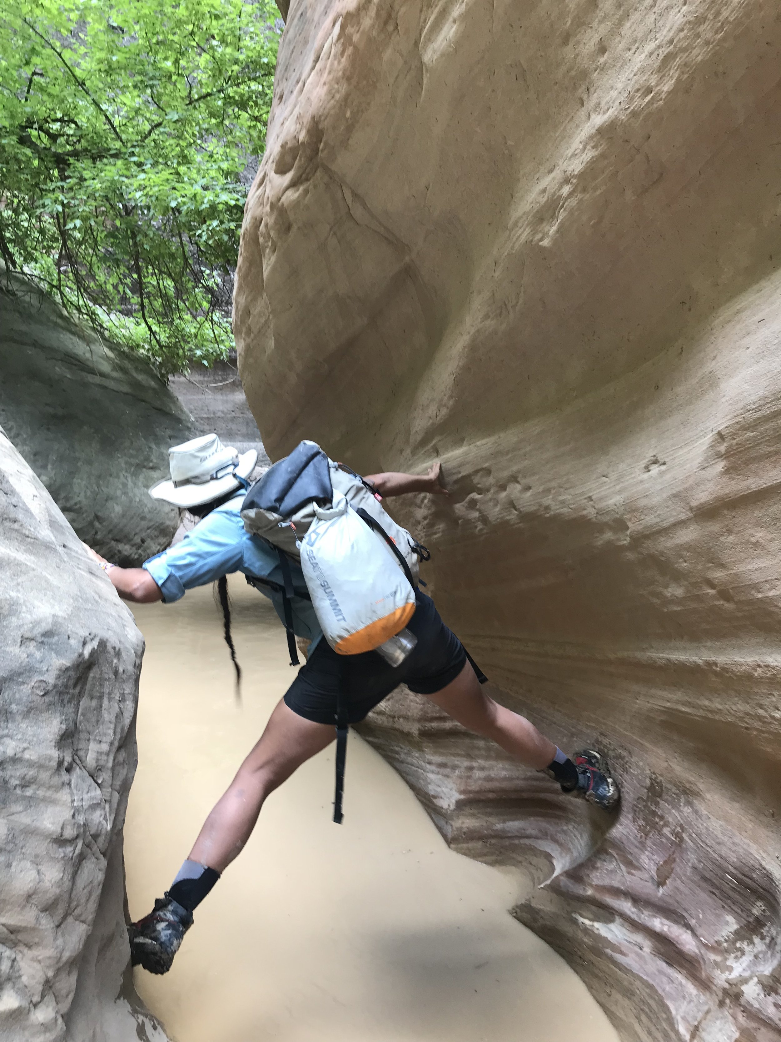 Celie climbing her way over a pool in Orderville Canyon.