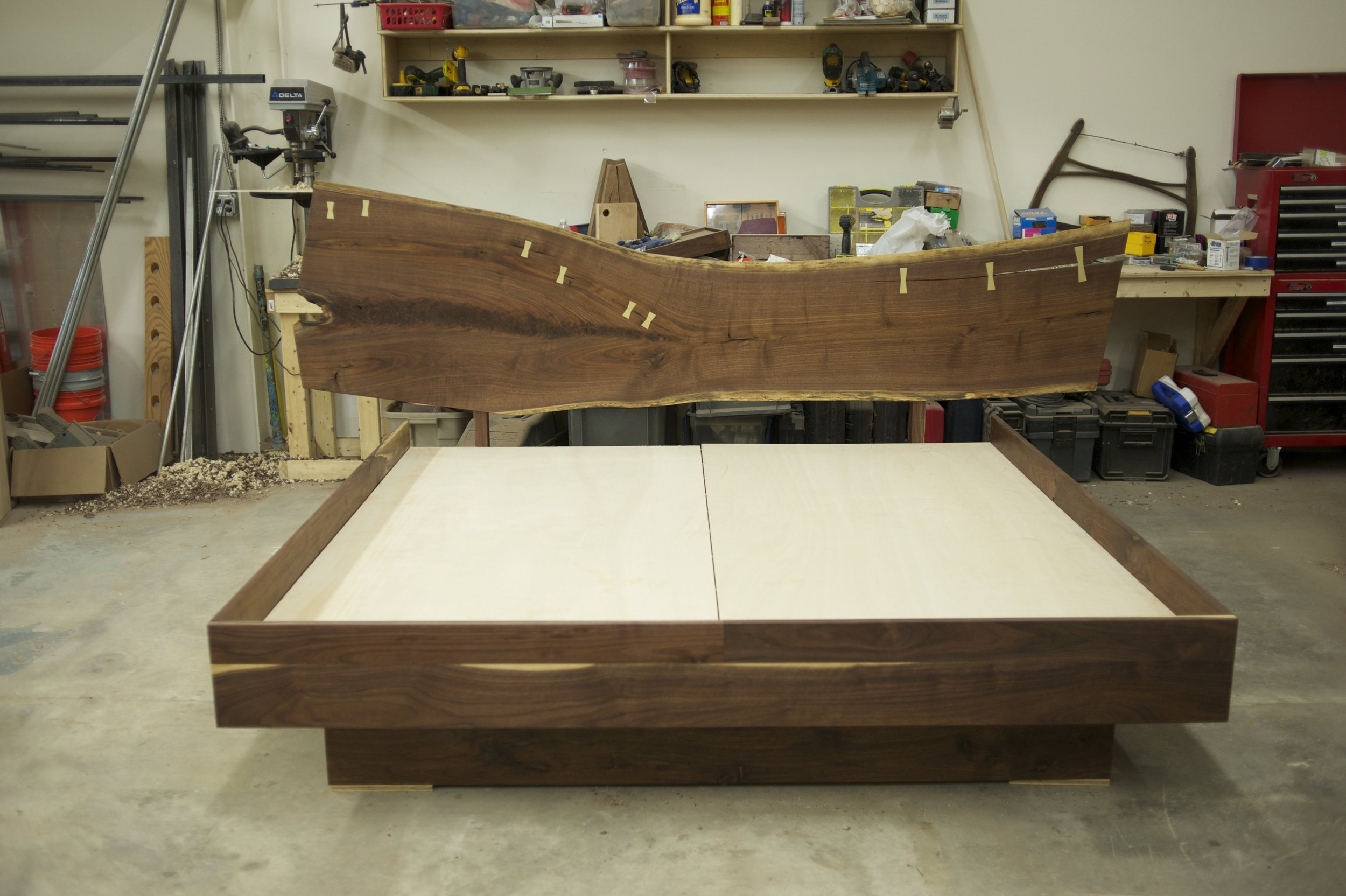 Live-edge walnut bed with solid brass bowties.