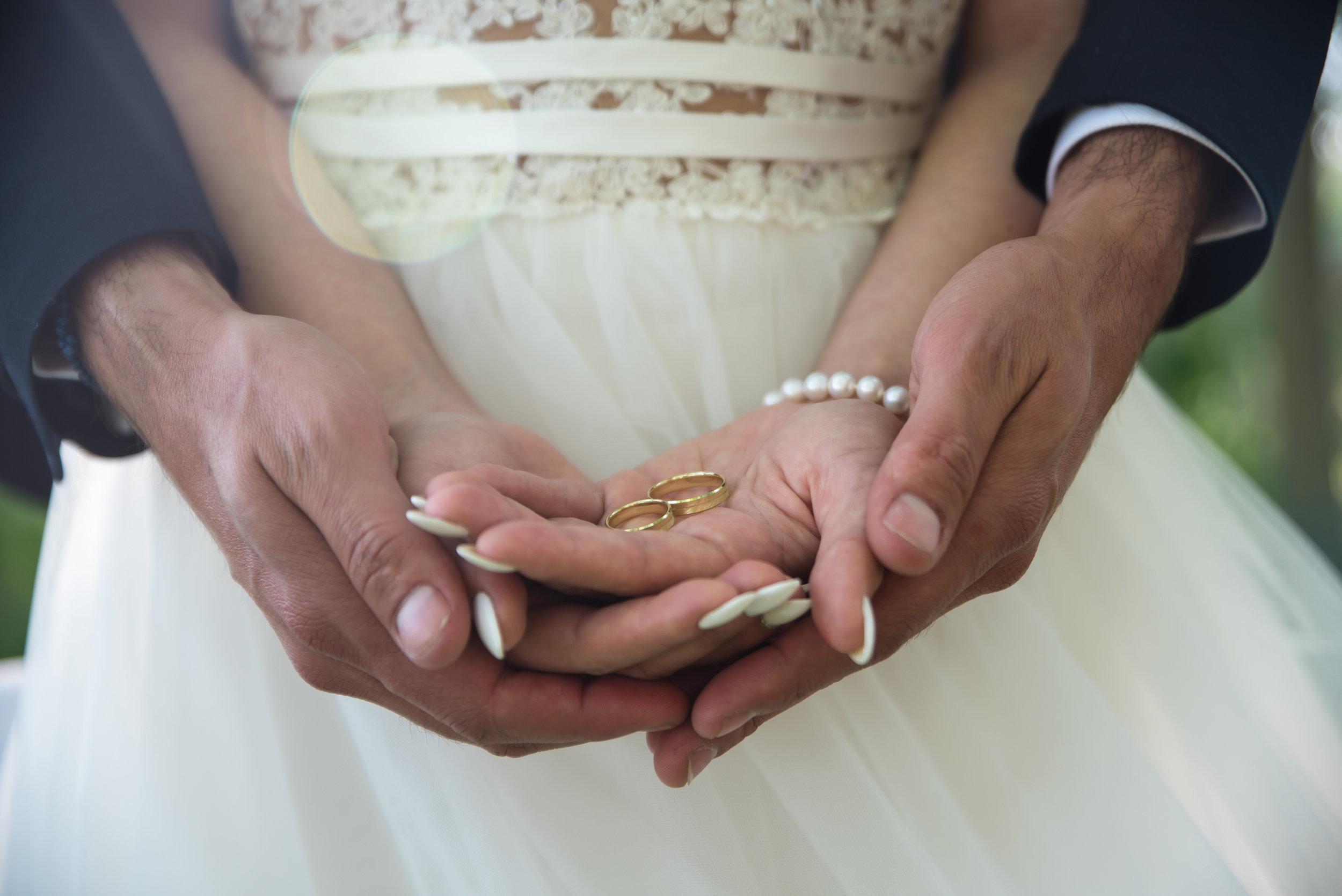 two-golden-wedding-rings-on-bride-and-grooms-2LGTWMJ.jpg