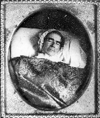 Black and white period photo of woman in nightgown and nightcap after her death (common type photo of that era), set in oval frame.