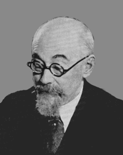 Image Description: Black and White photo of bald man with beard and glasses looking left and down, wearing white shirt with tie and dark jacket, eyebrows raised in interested expression.