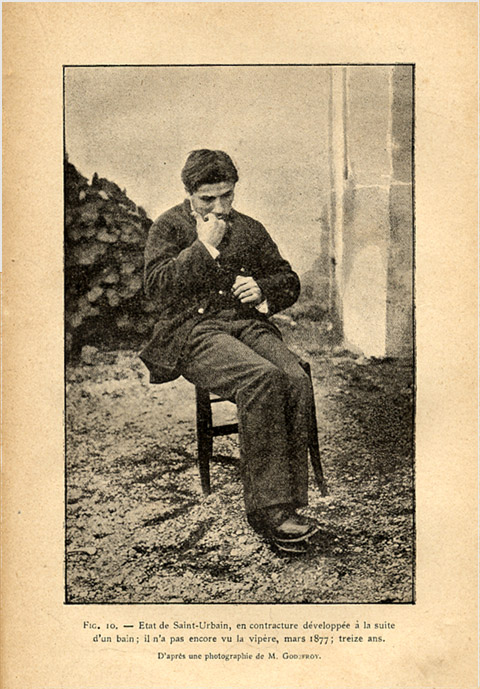 Image Description: aged browned page from a book, with a black and white photo of a young man in a suit sitting in on a stool, perhaps biting his fingernails on one hand. He has dark hair and is dressed nicely, with feet crossed and one foot over the other as if somewhat anxious or distressed. Photo appears to have been taken outdoors. Some French lettering underneath the photo.