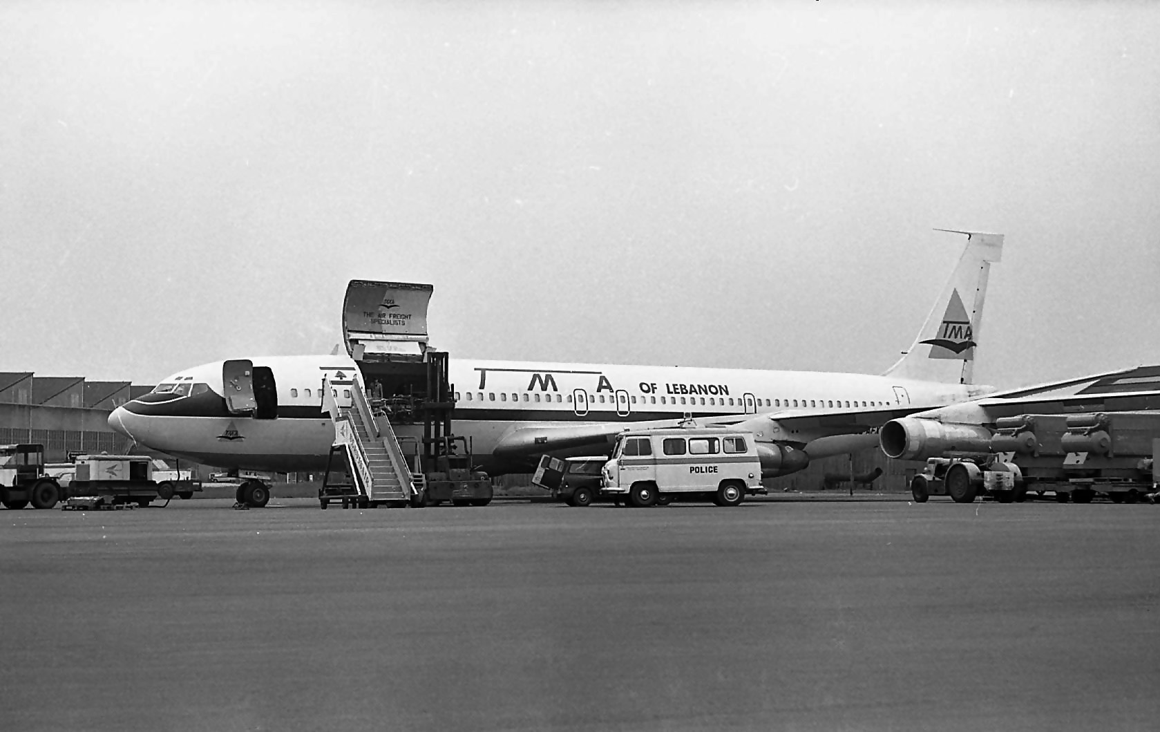 TMA Boeing 707 freighter OD-AFX is being watched closely by the local constabulary whilst being loaded on Faireys Apron.15th March 1973. Bob Thorpe.