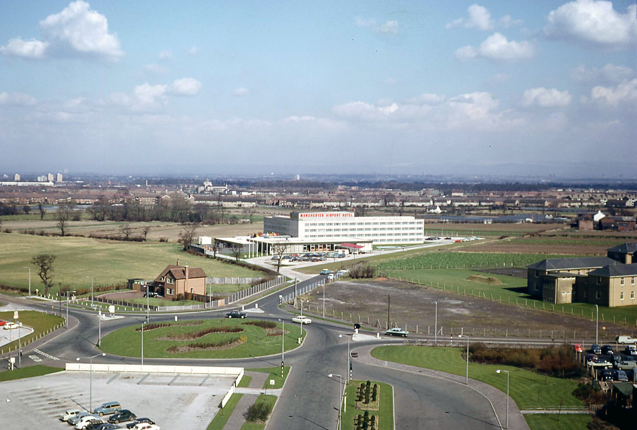"I've given up counting how many hotels there are nowadays (2019) around Manchester Airport.Well, in April 1966 it was pretty easy as there was only one. I'm not counting the Airport Pub although in those days it did actually offer a couple of rooms out on the top floor and I remember the landlady serving tea and toast to keen spotters as they watched the night freight flights from the corner room. Over the years (like they do) the hotel pictured has changed names and ownership several times.I think today its called the Crowne Plaza (Thank you Google!) in my day I remember it as the Excelsior. But we have here a wonderful photo it time by Bob Thorpe showing how different the skyline has changed since the photo was taken 53 years ago. It's worth pointing out the former ""RAF Barrack block"" in the bottom right hand corner and what was the Airport Directors house in the left…perk of the job in those days!"