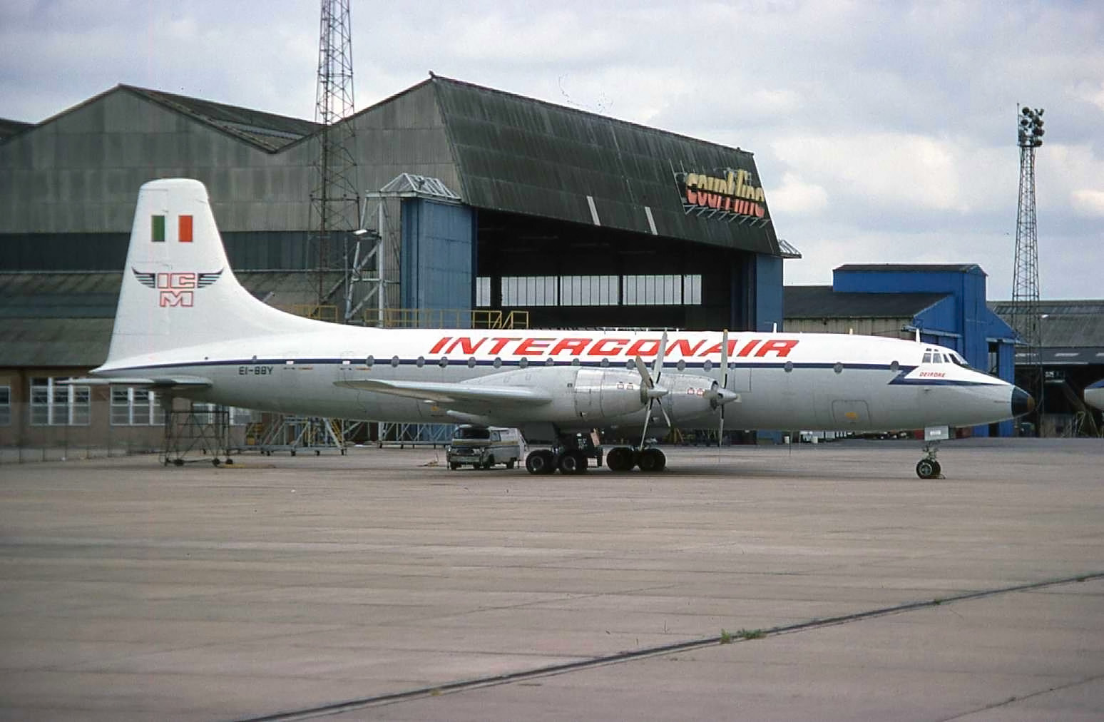 """The famous Court line hangar and an Interconair (Ex RAF) Britannia EI-BBY parked outside . Luton Airport August 1976. On a visit to Luton only last week (August 2019) I was recalling seeing Cubana Britannias in this very same spot and driving down from MAN to catch a glimpse of the rare beasts!  A quick check with the Security Guard on the gate…""""Any chance of a quick walk on the ramp for a picture of the Brit?"""" …Sure no problem! In fact our early coach trips got permission for a drive around the ramp at o'dark thirty in the morning.Oh yes those foggy cold Winter mornings at Luton. I remember them well.."""