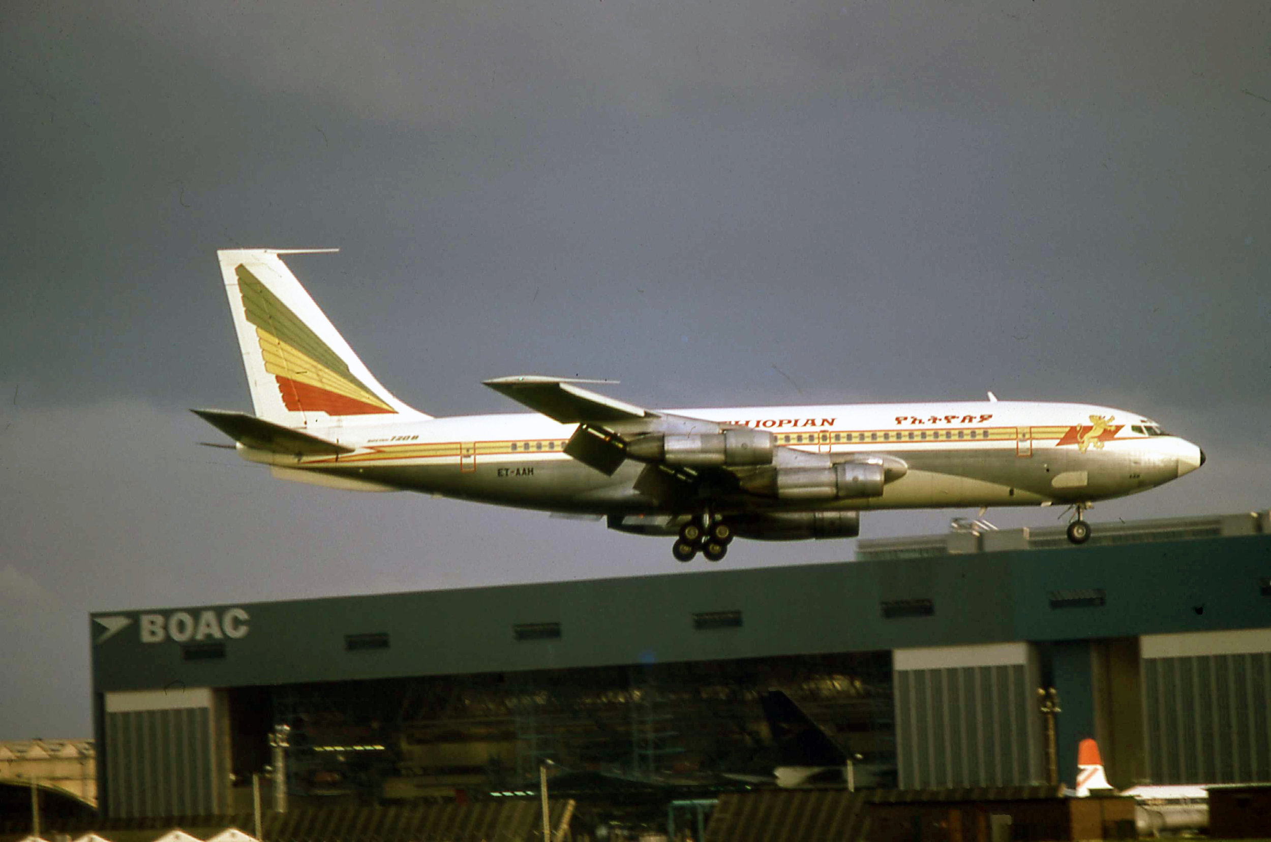 """Ethiopian Airlines Boeing 720 ET-AAH landing at Heathrow in September 1974. With a BOAC 747 classic where else but in the BOAC hangars at the rear and the """"training Comet"""" outside…nostalgia at its best?"""