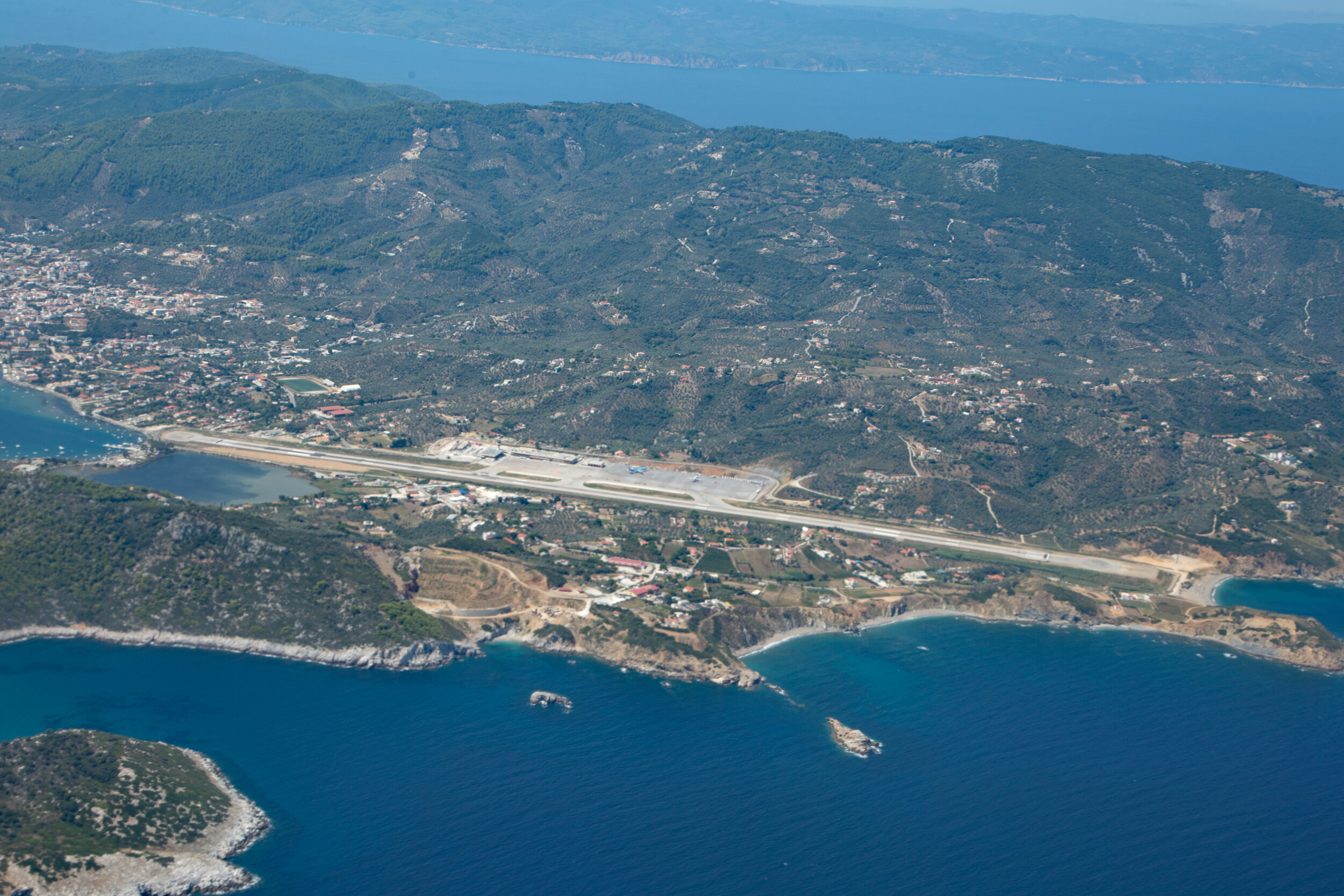 An aerial view of the airport taken by Peter H from a TUI B757-200 in Sept 2019. Skiathos town and the Amaretto Cafe Bar are located to the left as you look at the Runway.