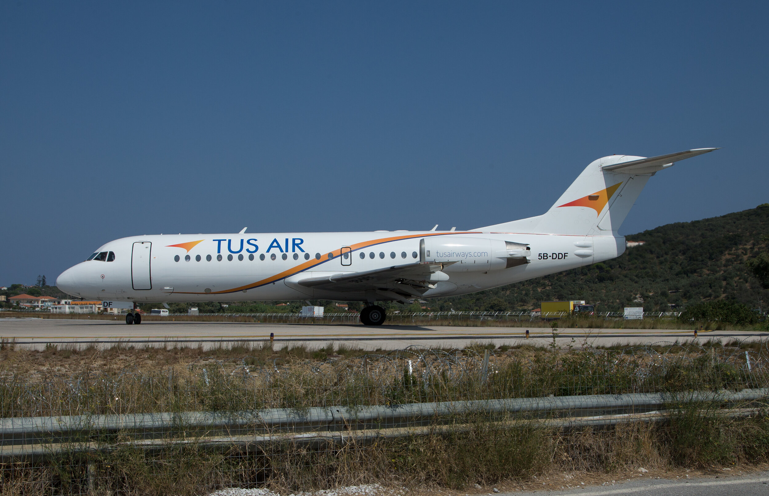 """The """"typical"""" line up shot from the Amaretto Car Park for a Runway 01 departure. TUS Air operate the Fokker 70 on services from Tel Aviv to Skiathos.Photo: Peter H"""