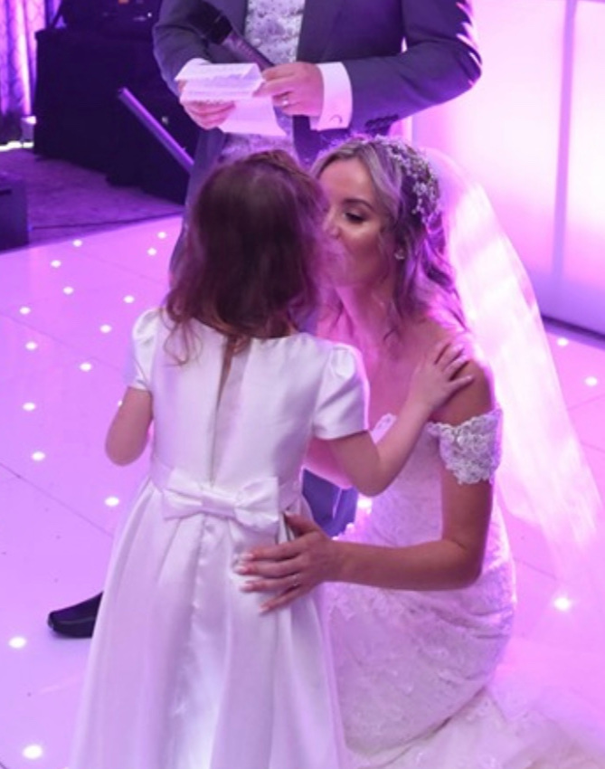 A lovely moment with soft lighting for the bride and her flower girl with soft bespoke lighting