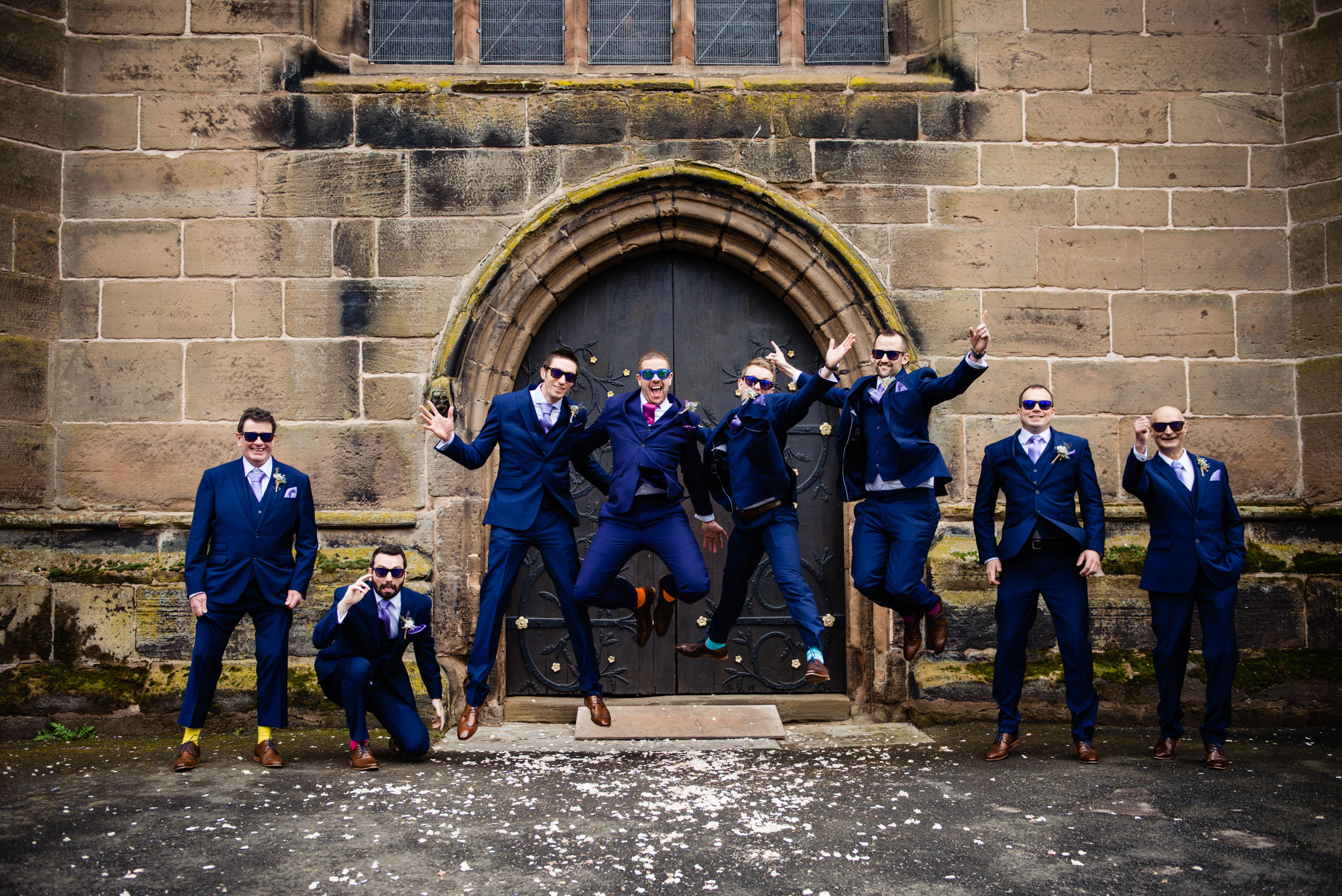 Fun groomsmen jumping in front of Church door during group photo