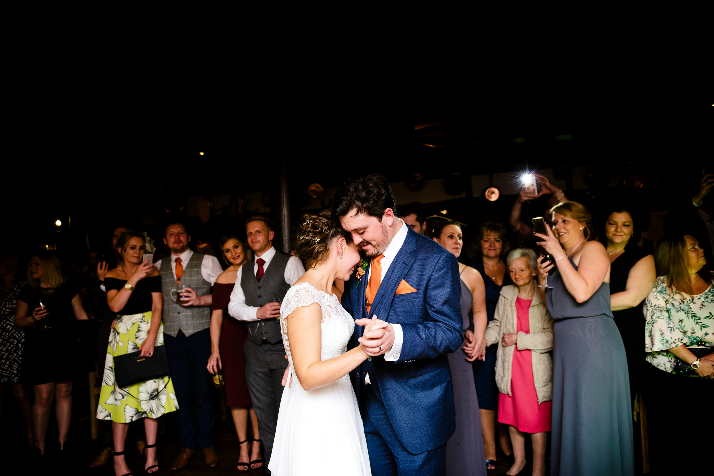 Newlywed couple holding each other lovingly during their first dance at Arrow Mill