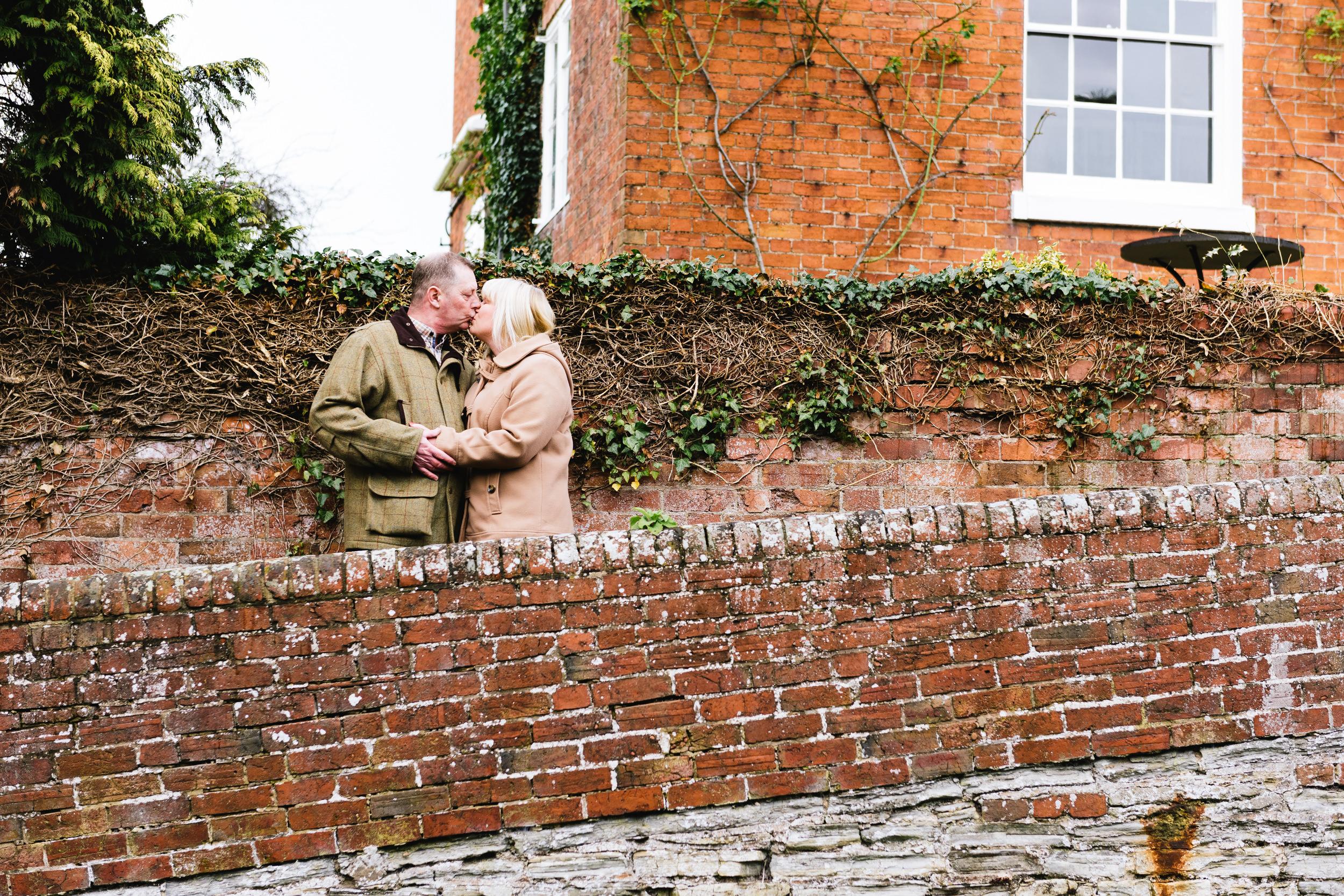 Older couple kissing stood on zig-zag outdoor brick steps