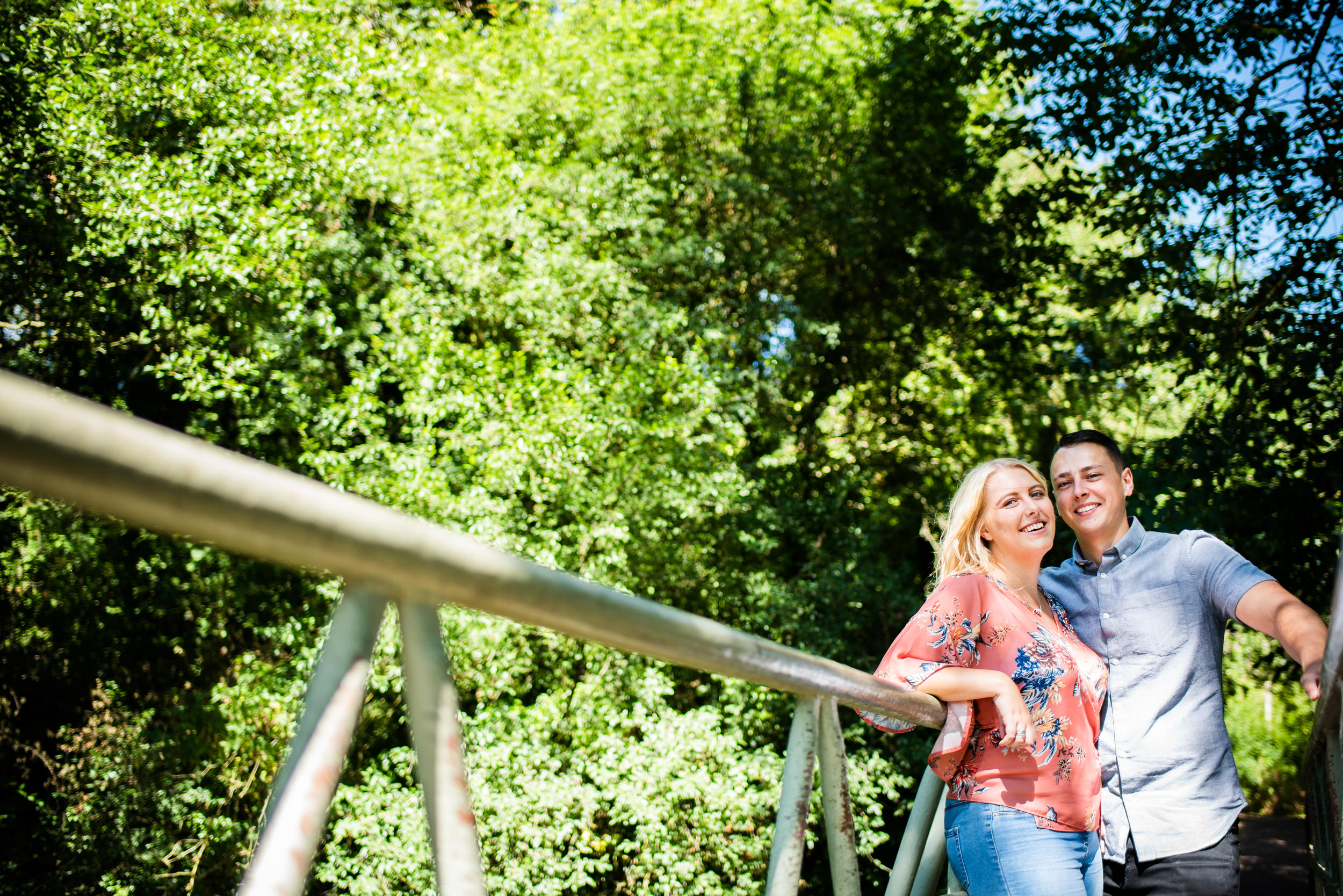 Man with his arm around his partner leaning on a metal bridge railing