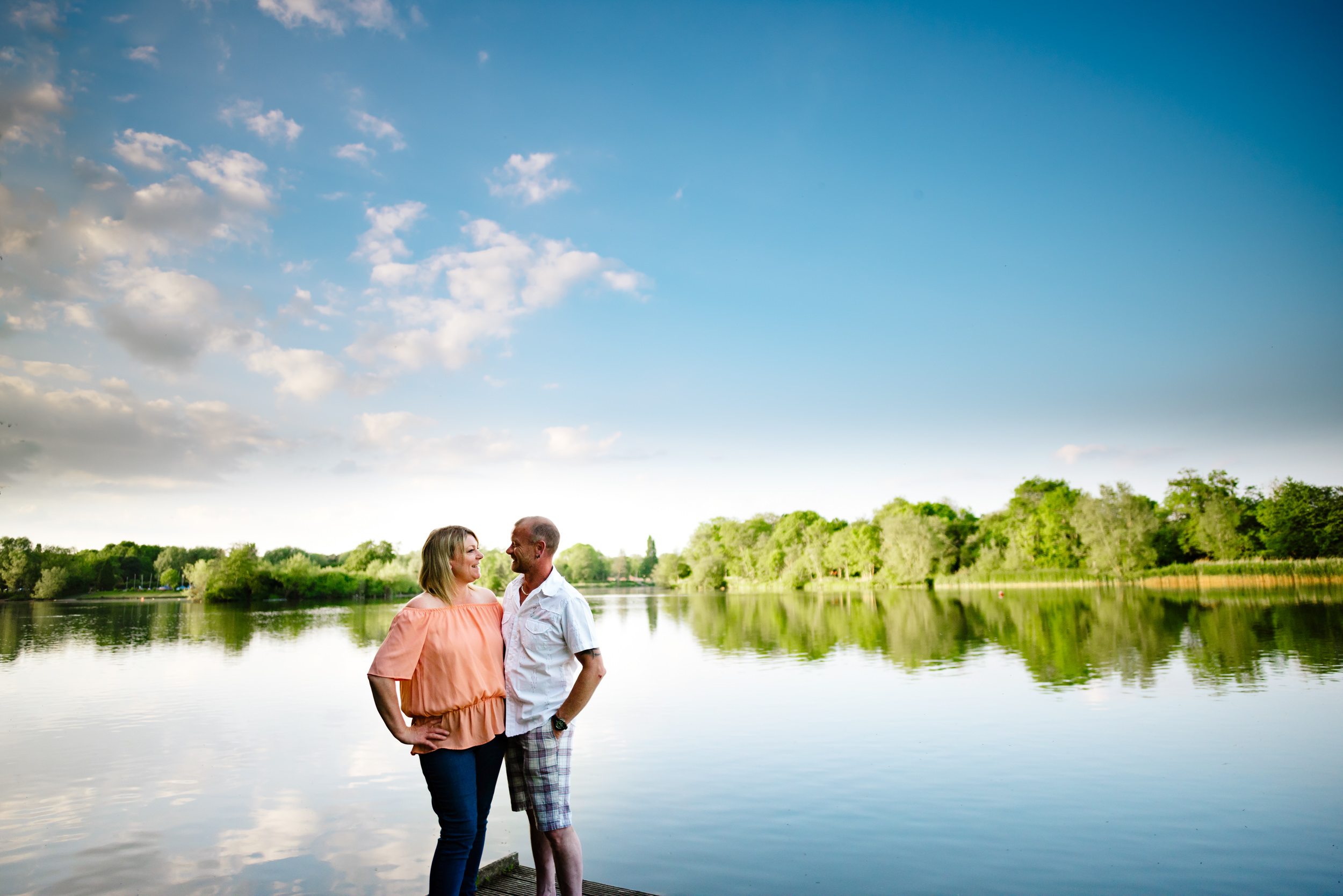 Couple on a jetty into a serene lake laughing