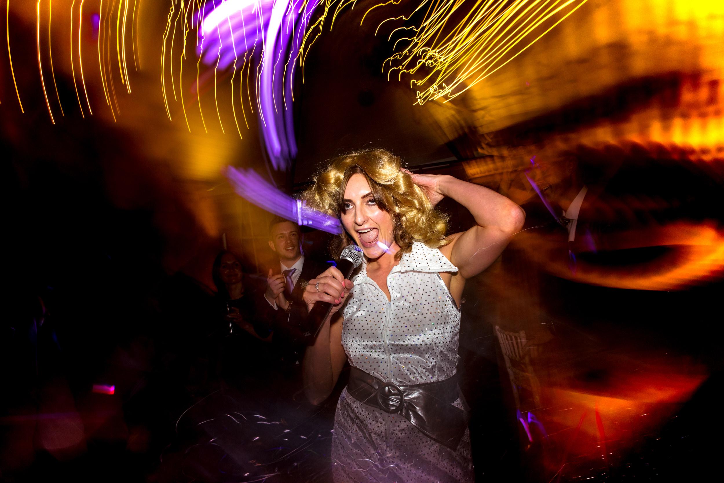 Evening wedding guest dressed as Abba on dance floor