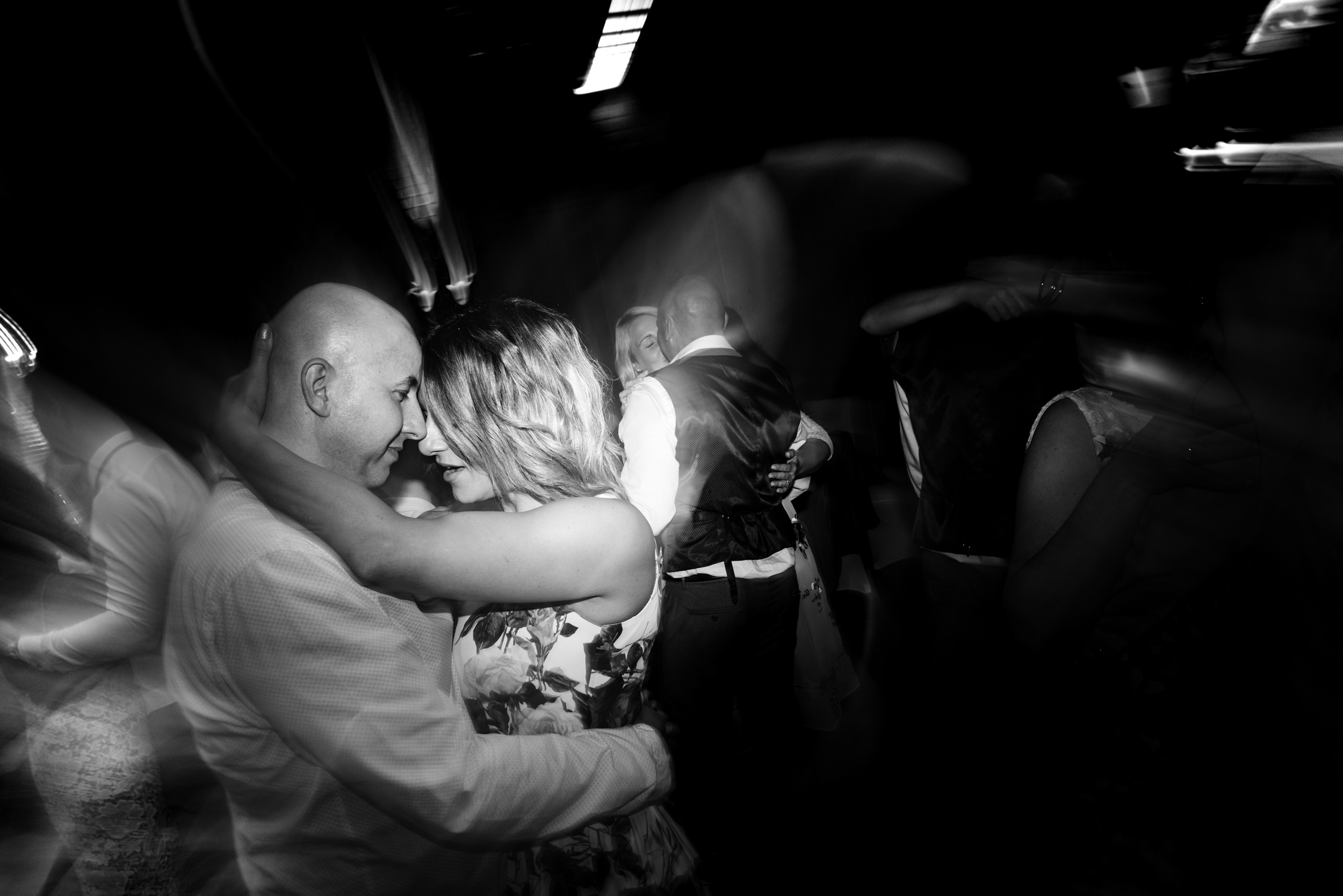 Couple kissing on the dance floor at the evening reception