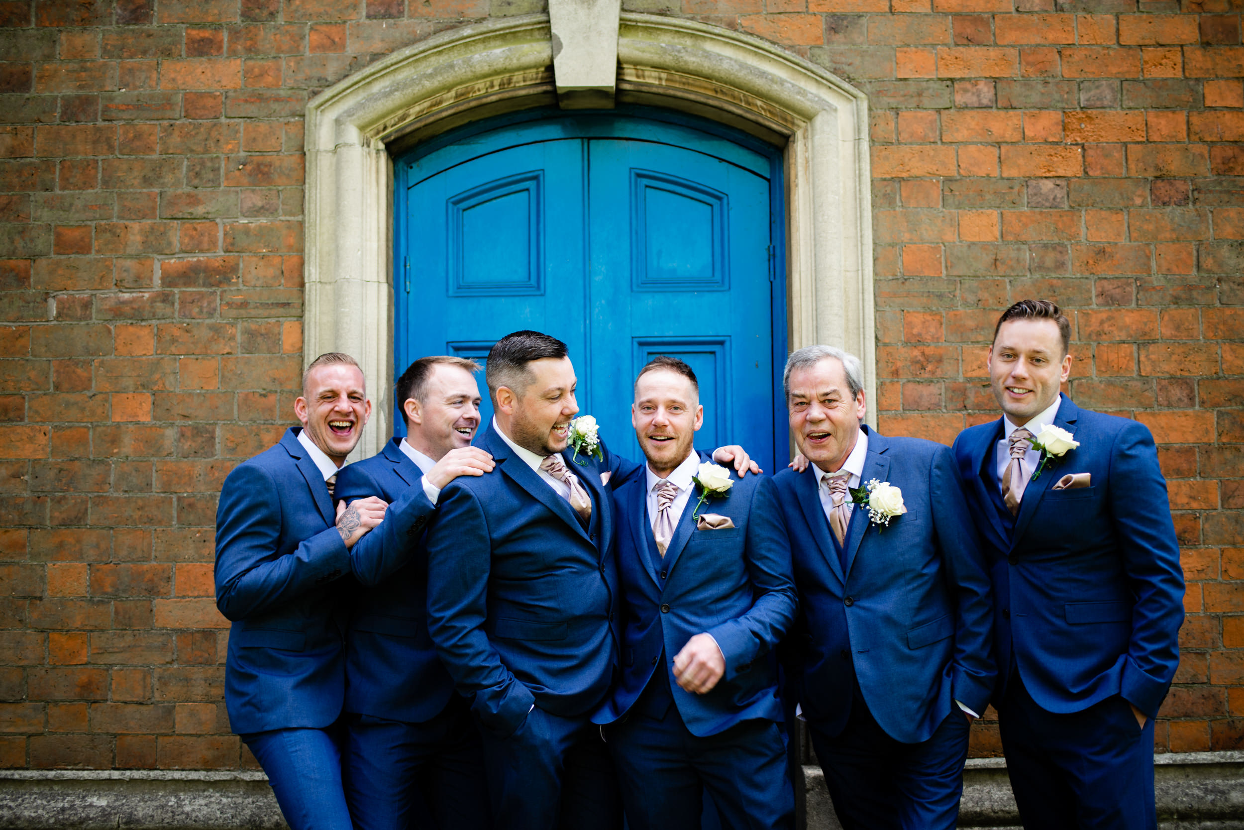 Groom best man and ushers laughing and joking before wedding ceremony