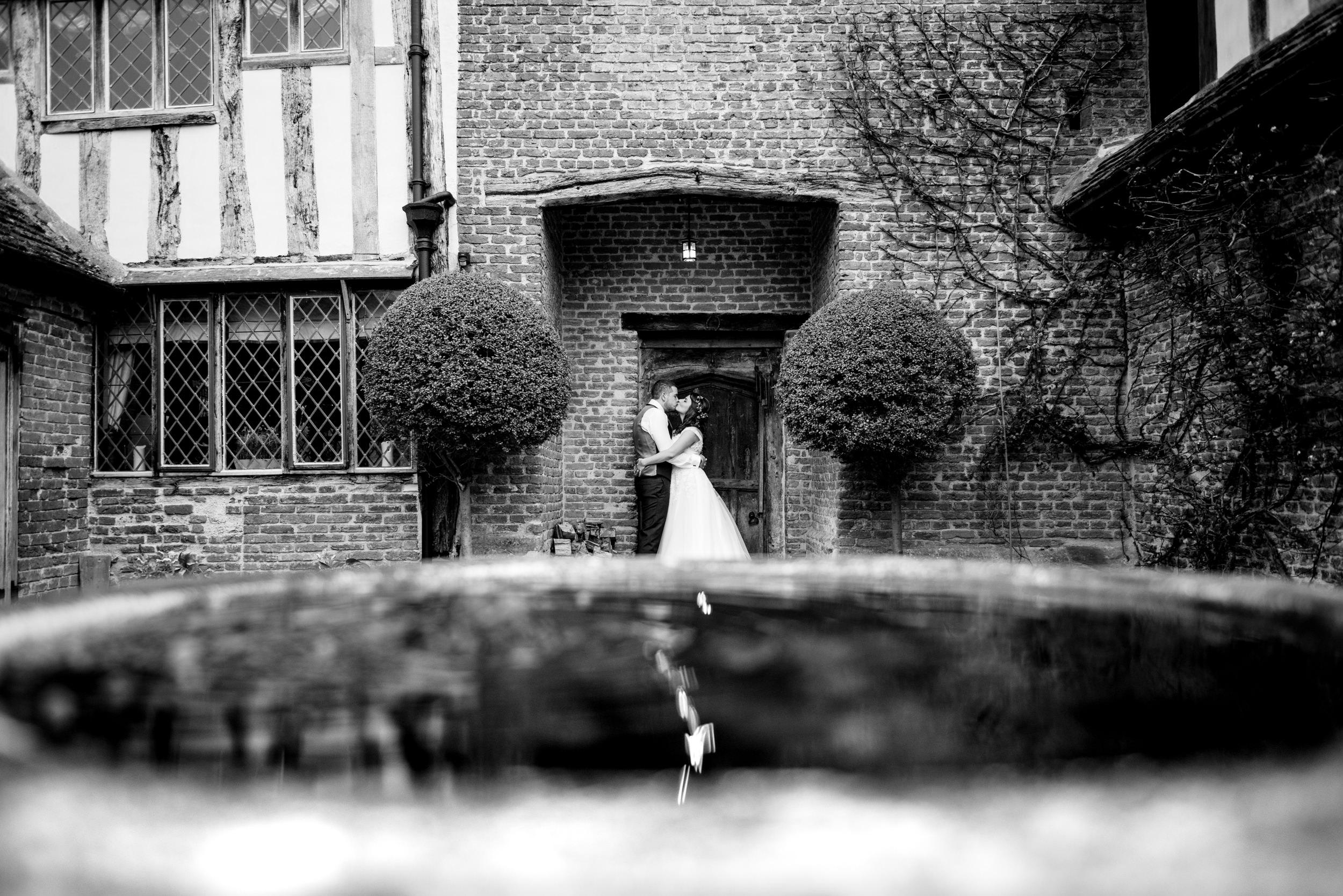Newlywed kissing and reflected in a bird bath at Grafton Manor Worcs