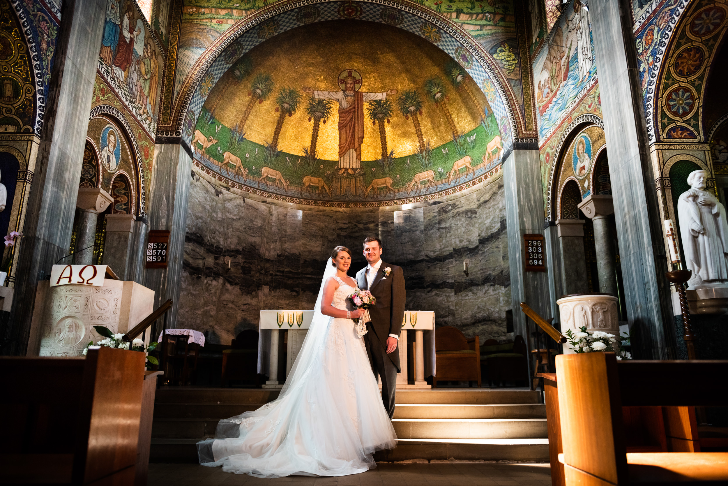 Portrait of Bride and Groom in front of the Altar of a colourfully decorated church