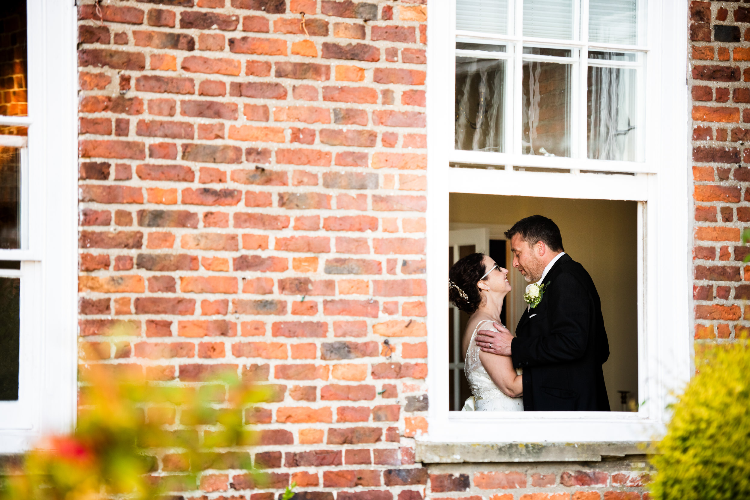 Outside portrait  through a window of a newlywed couple holding each other inside