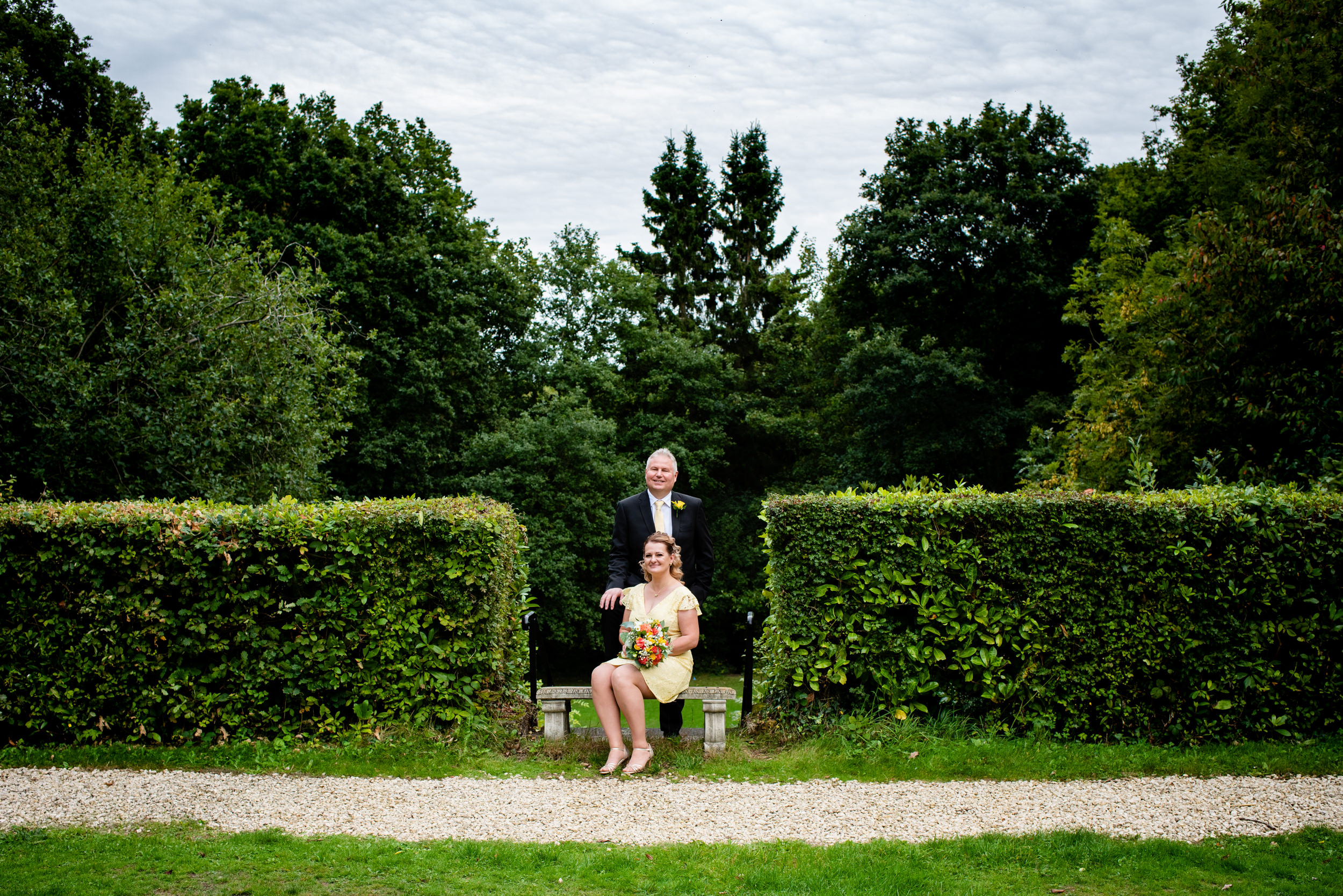 Sitting Bride with groom affectionately resting hand on her shoulder at The Southcrest Manor Redditch
