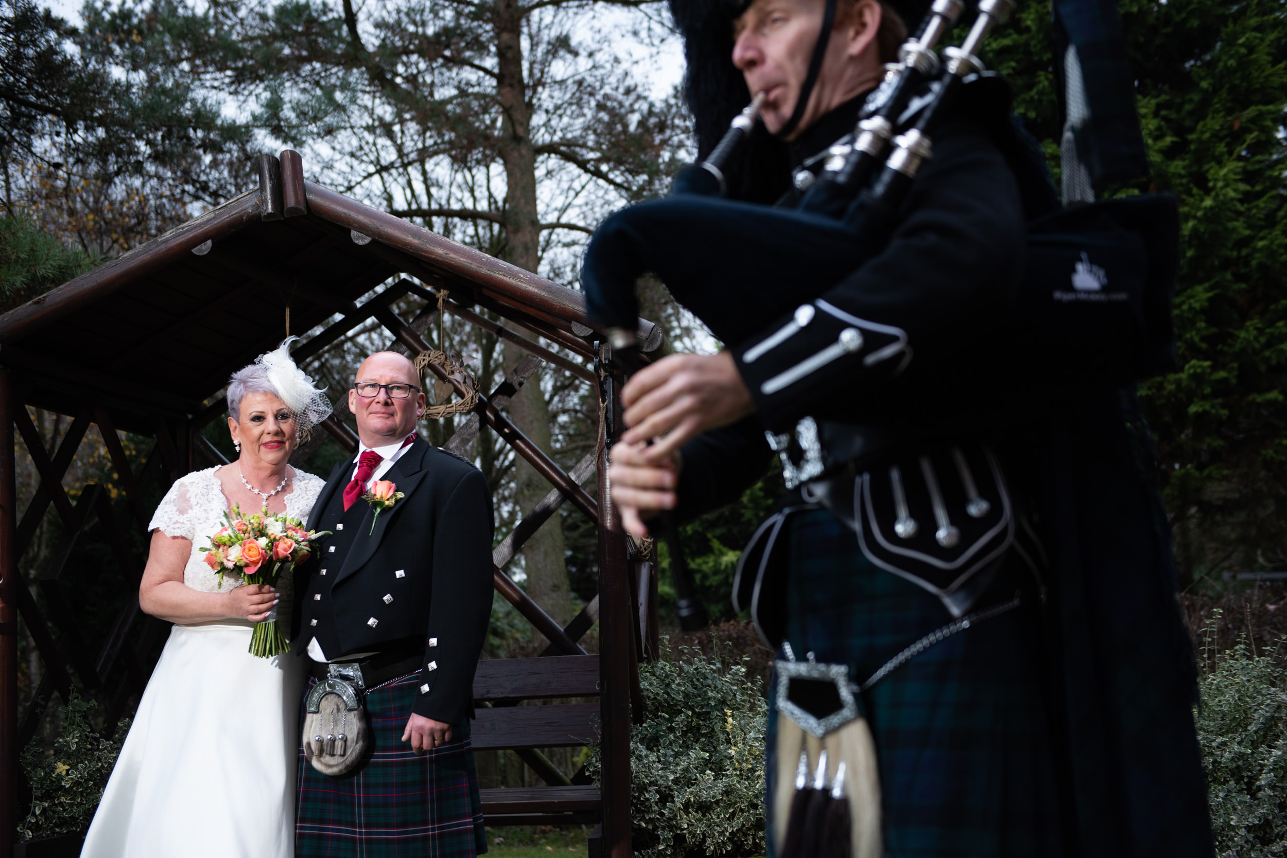 Newlyweds watching a Bag Piper playing outside