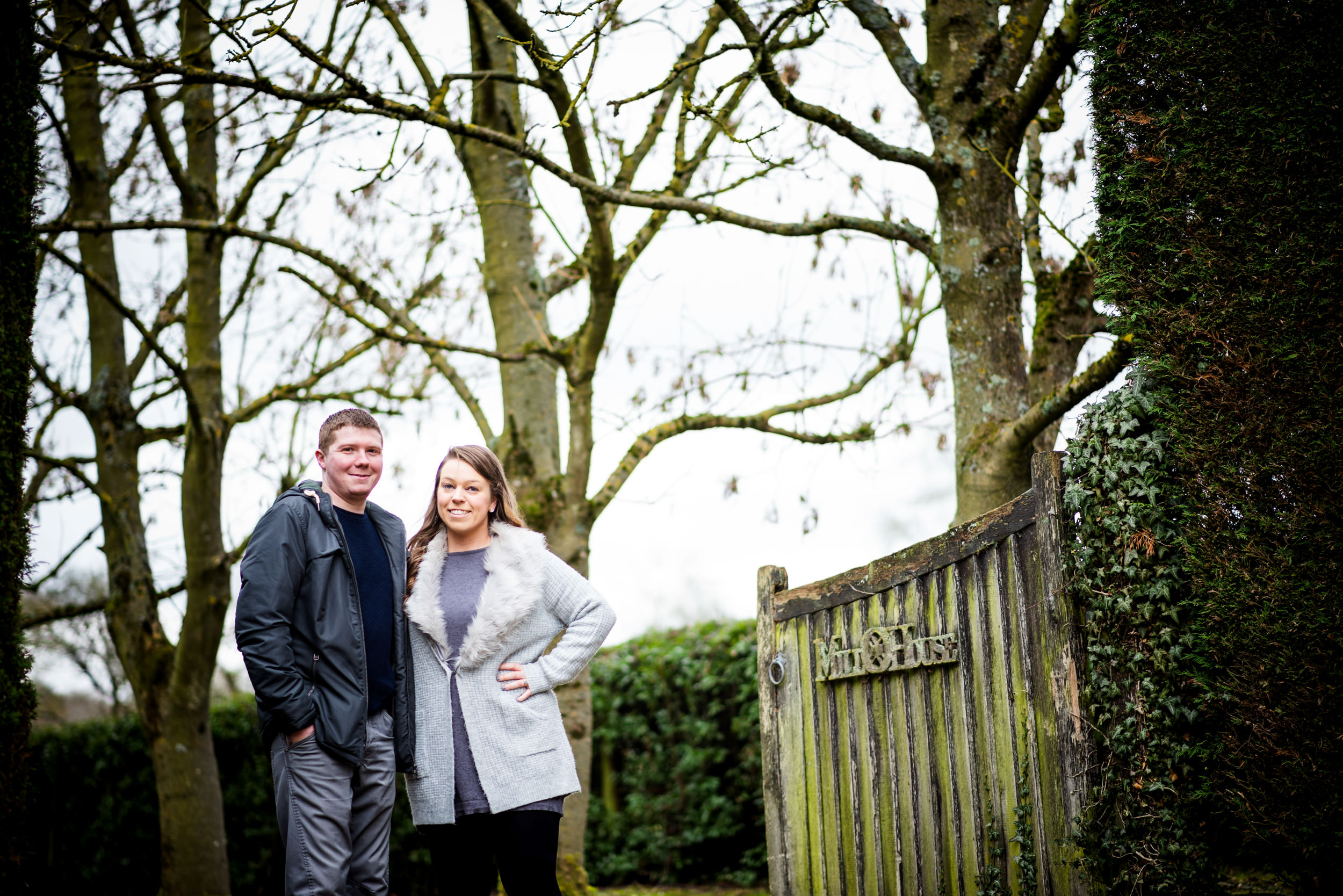 Smiling couple stood in a wooded driveway