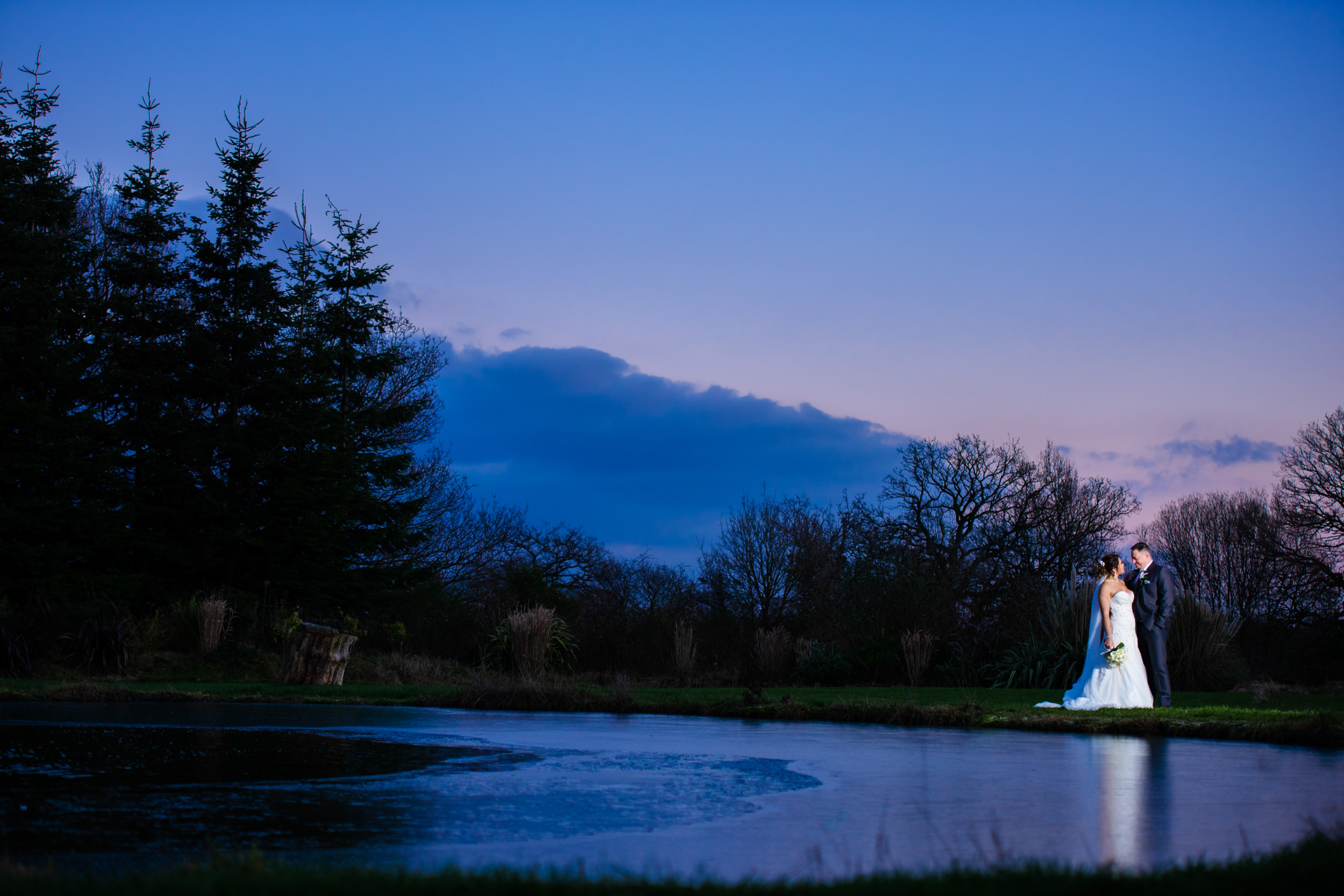 Bride and groom stood at the edge of a pond at The Limes Country Lodge Hotel at Twilight