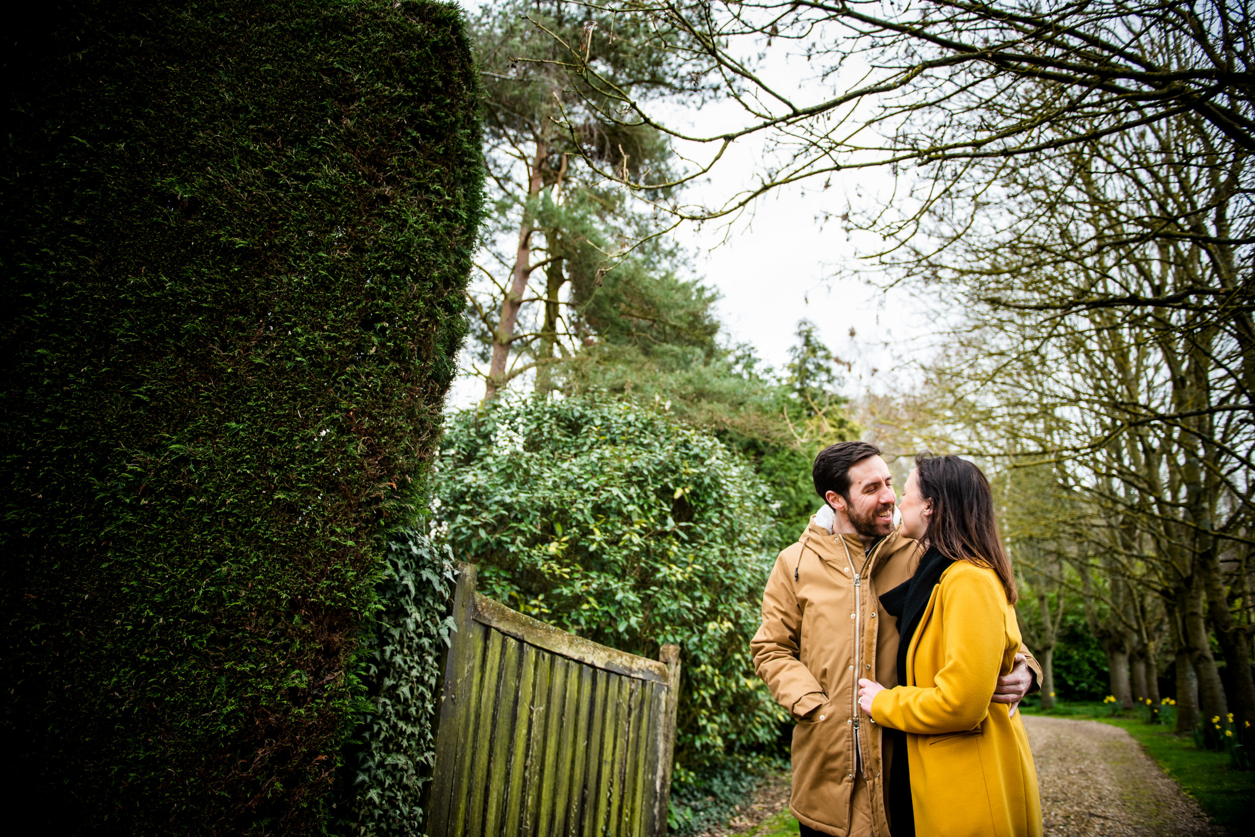 Engaged couple looking lovingly at each other in a wooded gateway