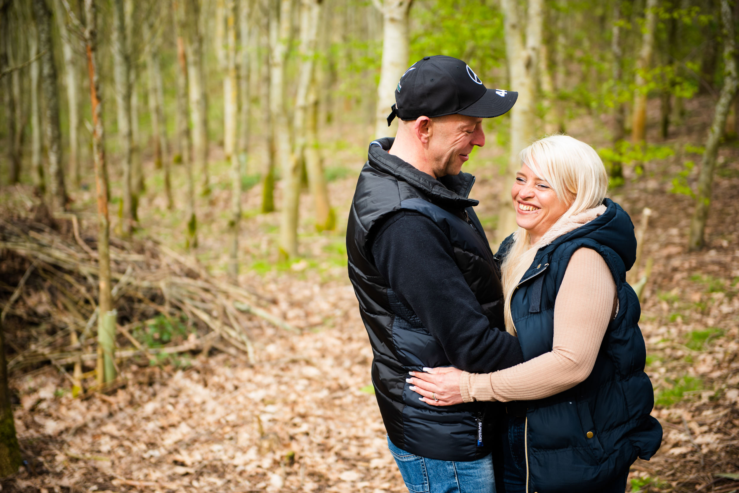 Engaged couple in a wooded glade laughing at each other
