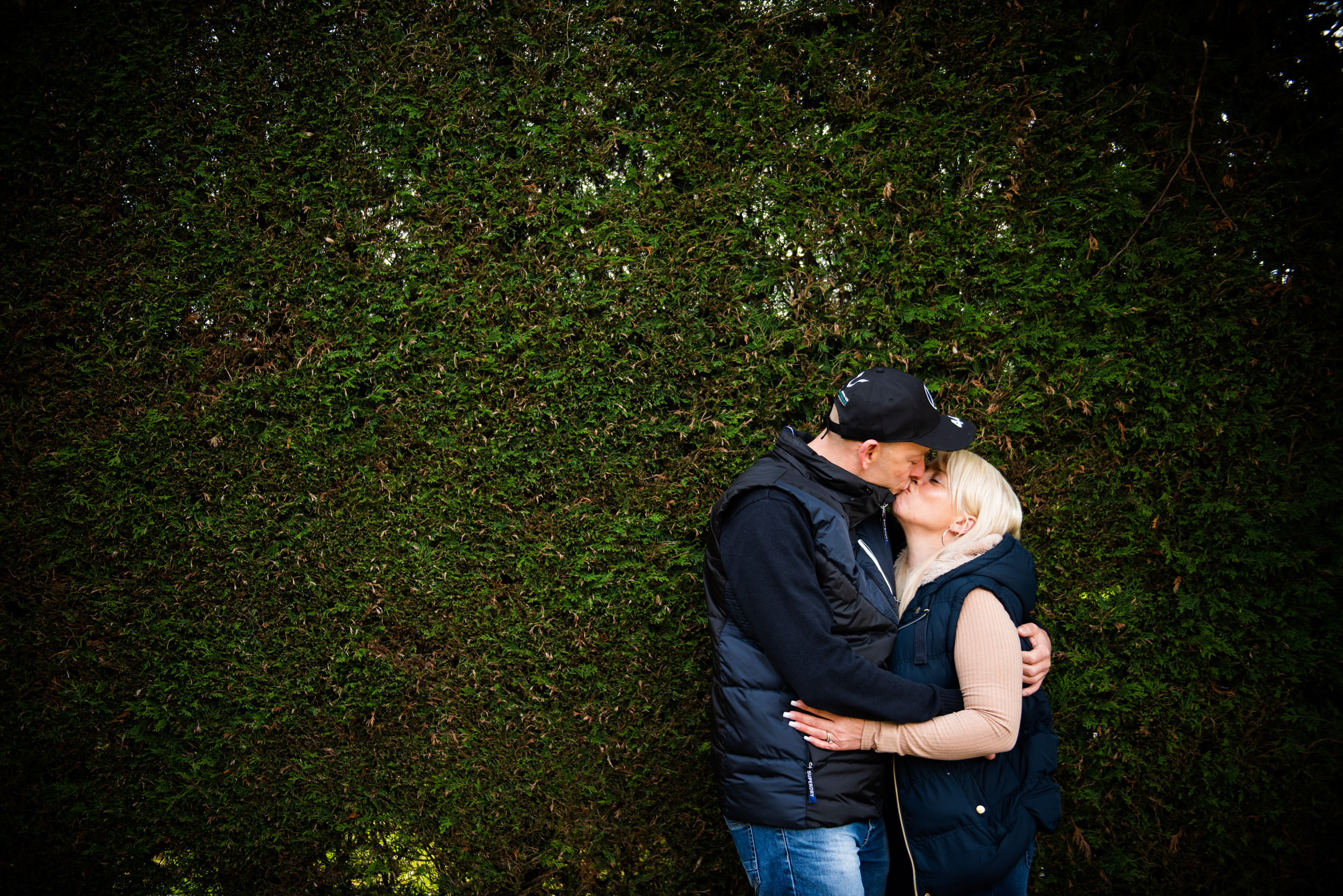 In love couple kissing in front of a bush
