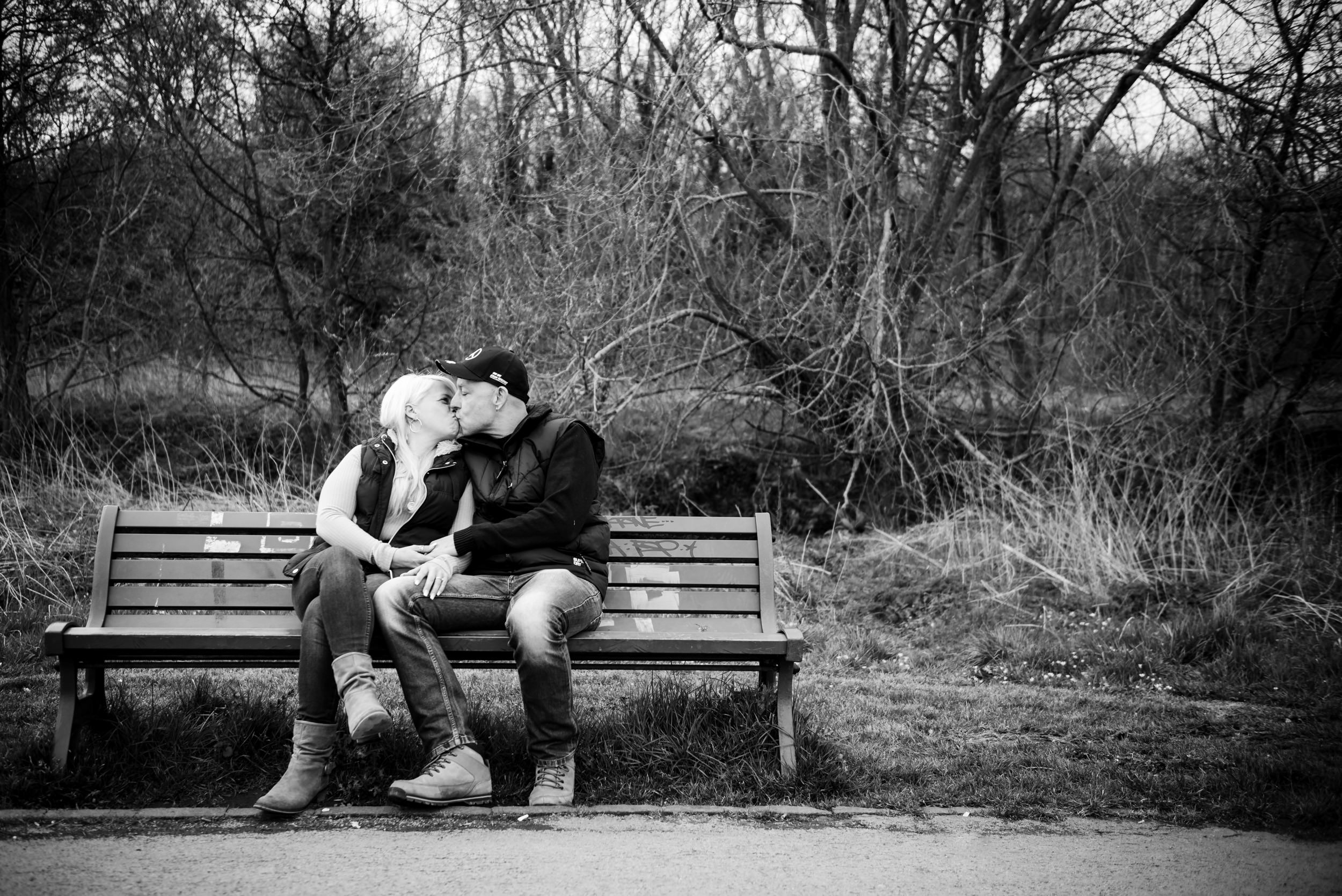 Couple kissing sat on a bench