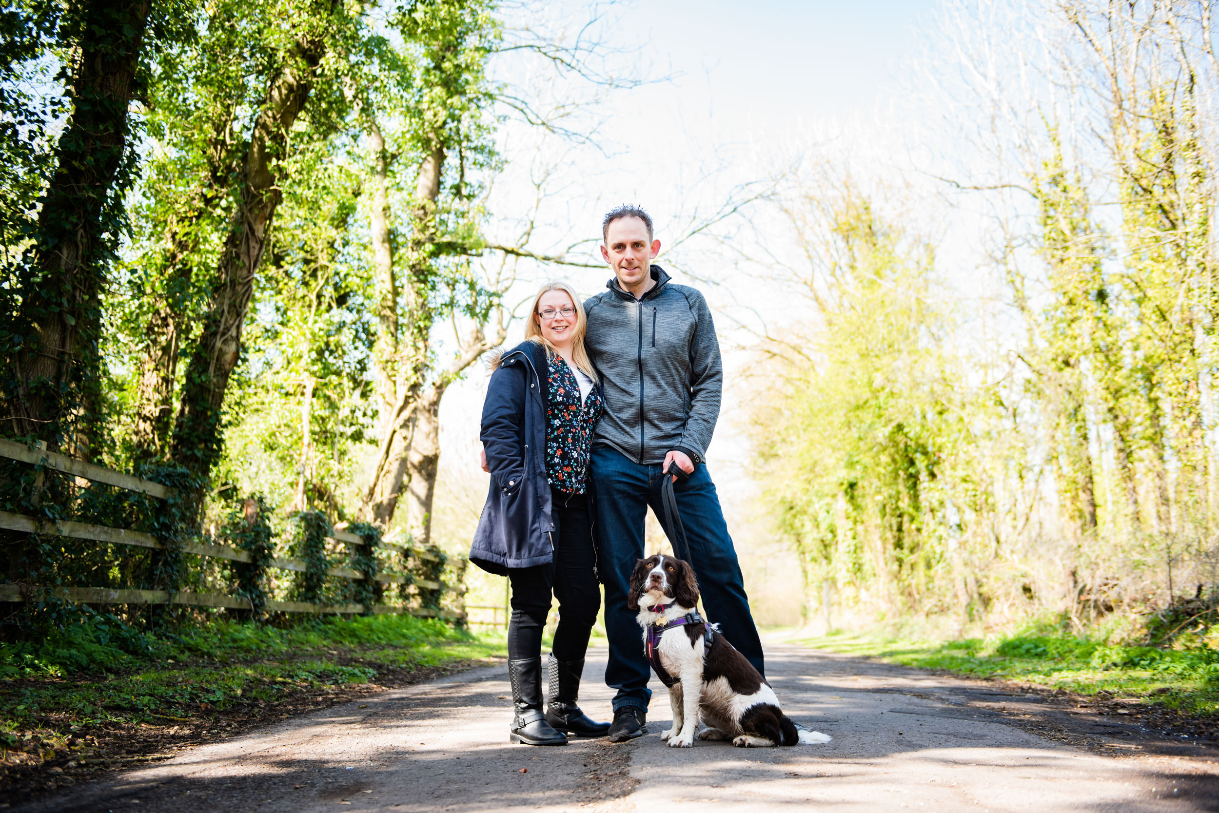 Engaged couple with their Springer on a wooded path