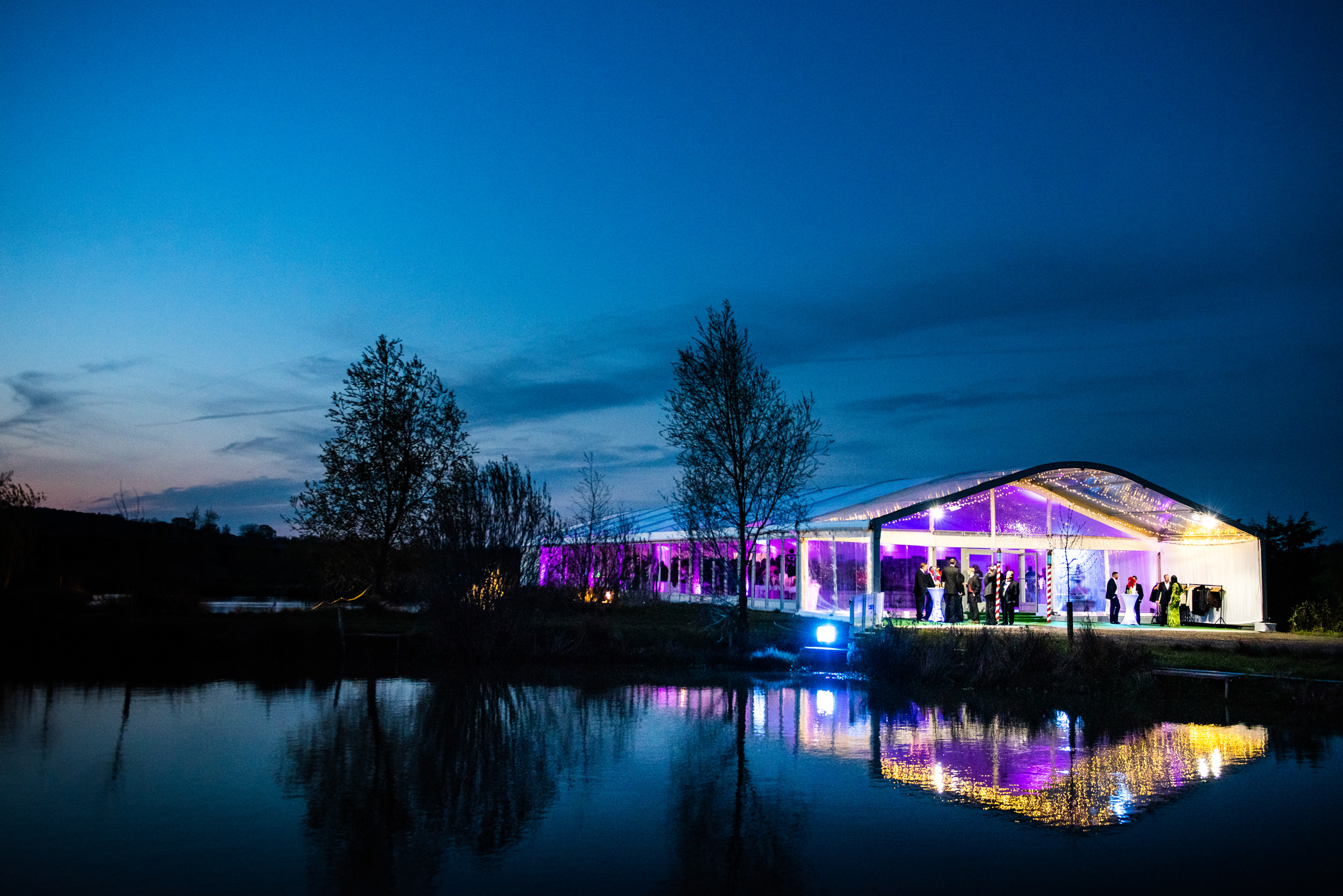 Evening shot of a Fews Marquee colourfully lit up against the night sky and reflected in a pond