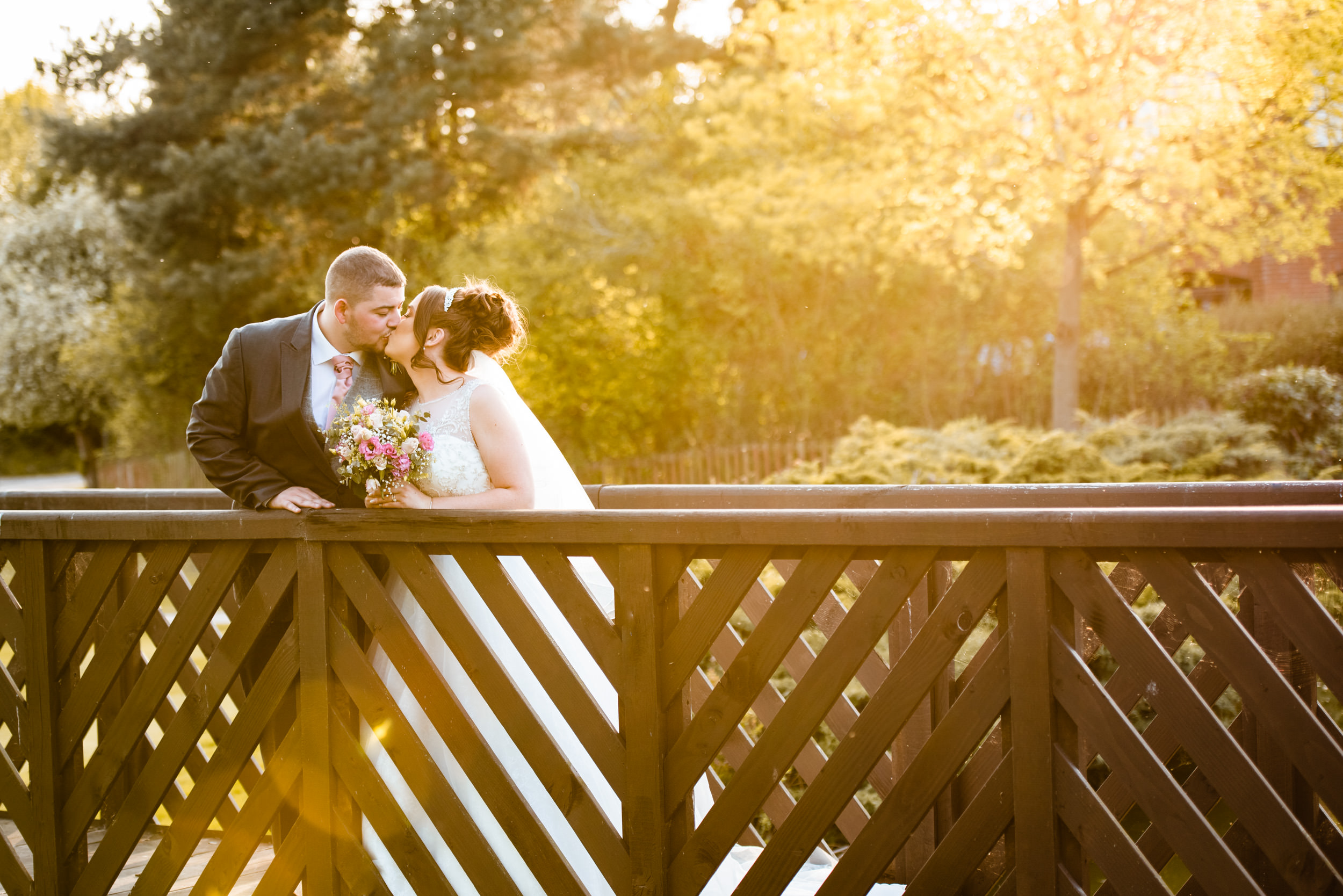 Bride and groom kissing on a wooden bridge in golden hour light
