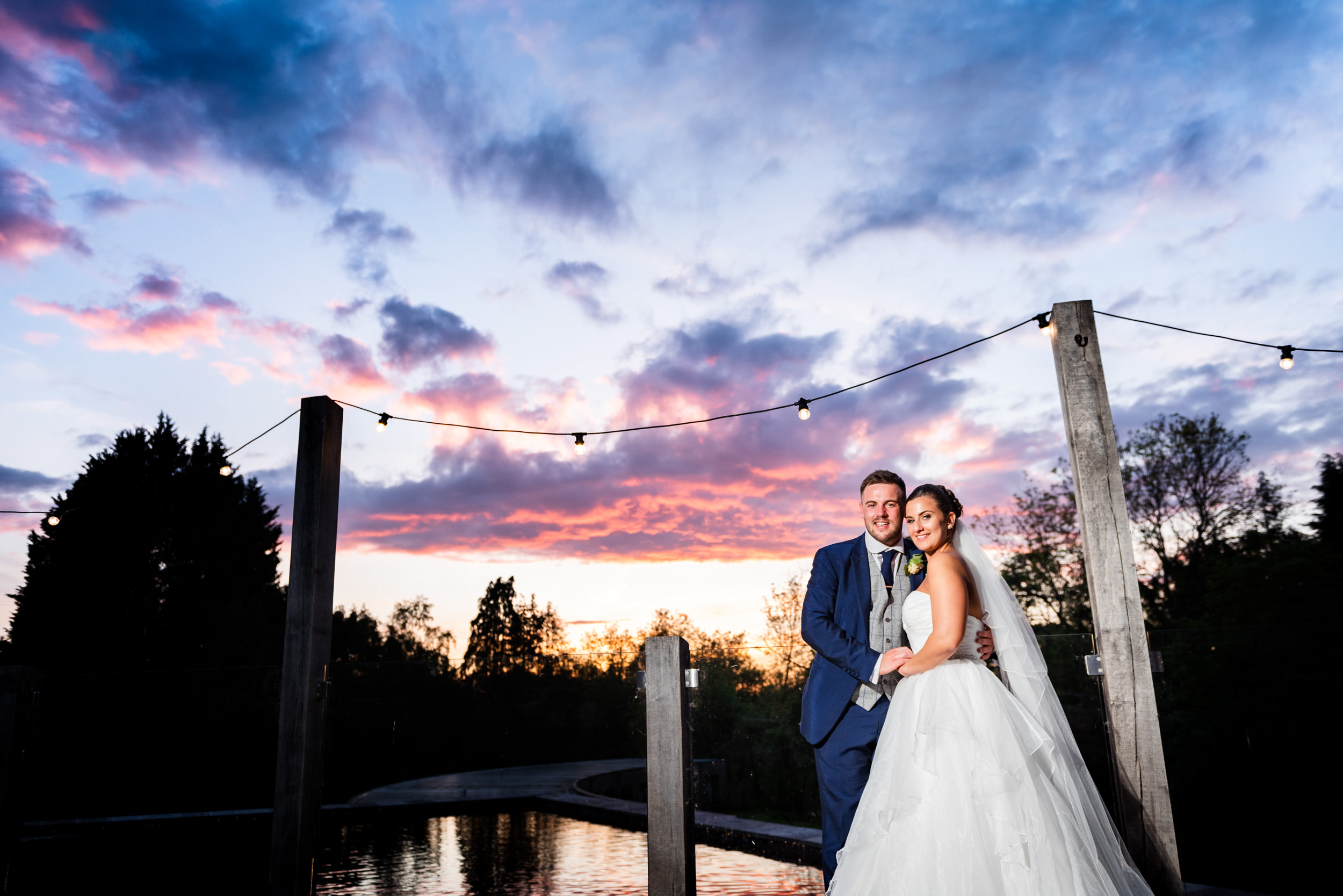 Groom holding his new wife in front of a dramatic sunset of pink and purple hues at The Mill Barns, Alverley