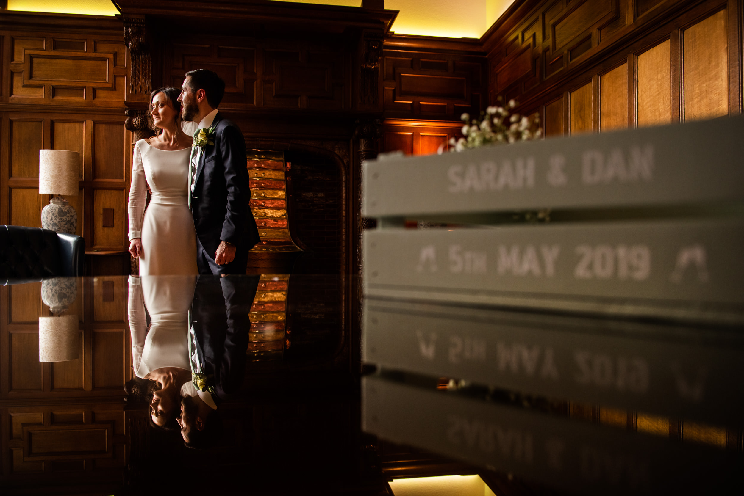 Newlywed couple looking out of the window in the dark wood paneled reception room at Pendrell Hall
