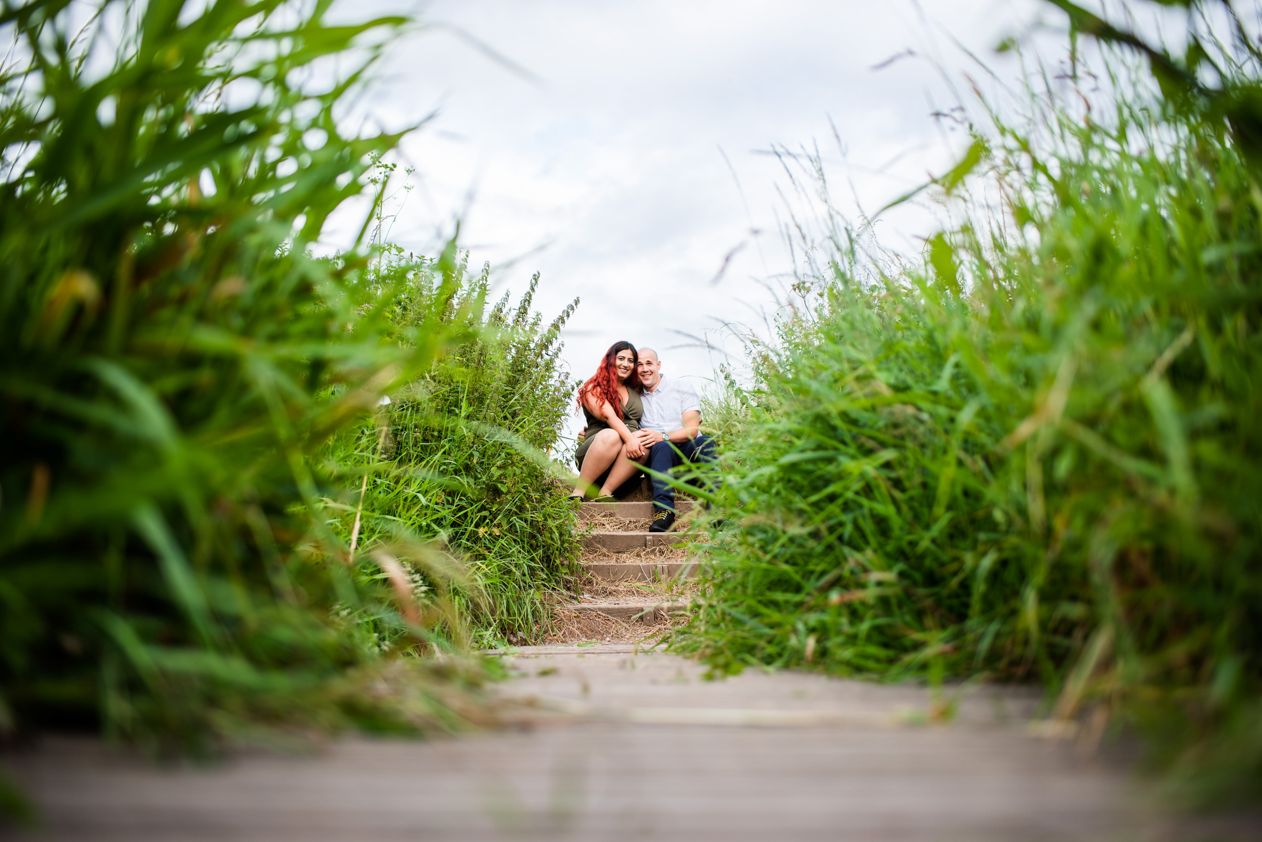 Engaged couple sat for their enagegment photography on some wooden steps at Arrow Valley Lake, Worcestershire