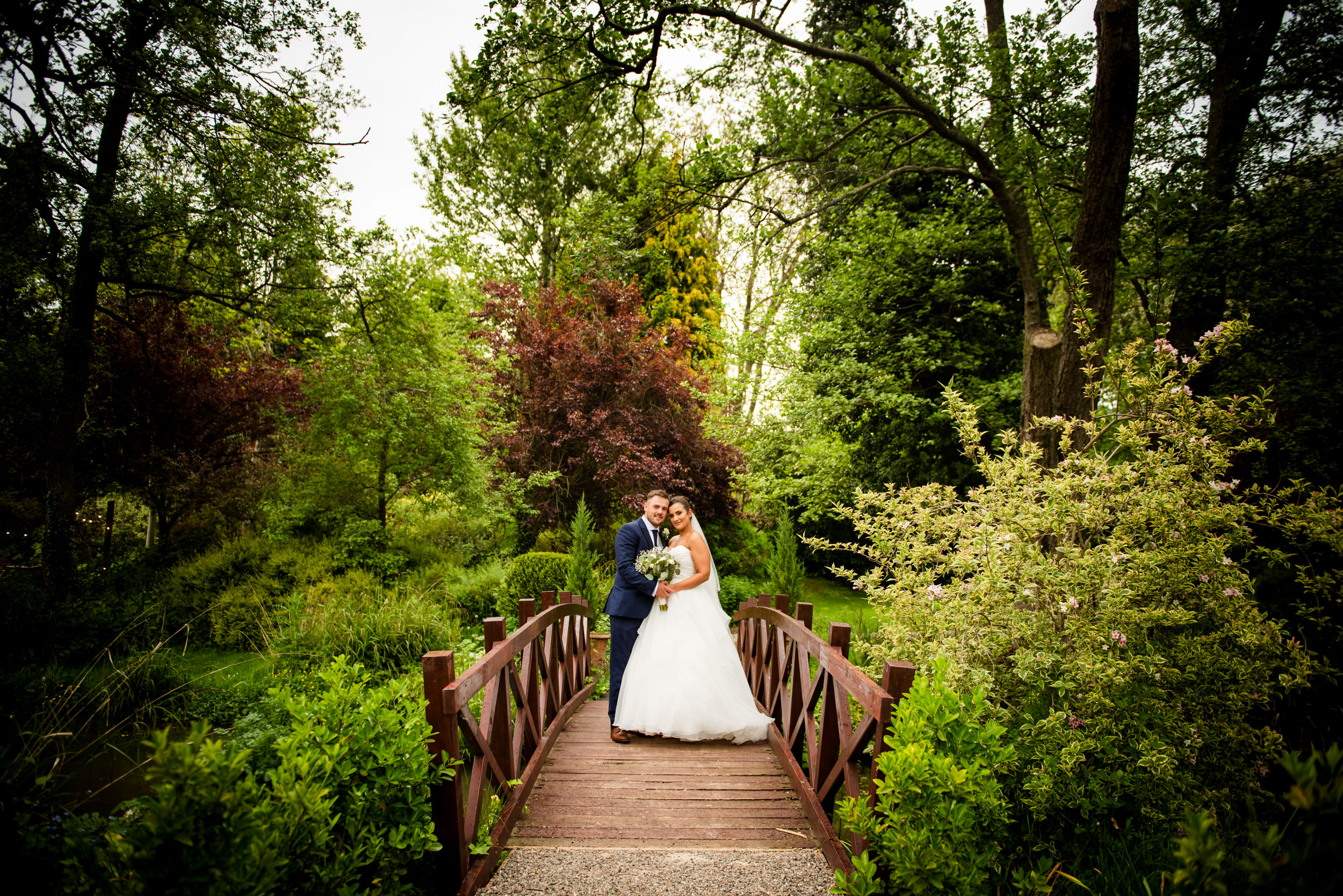 Newly married couple stood on a feature Bridge at The Mill Barns, Alverley