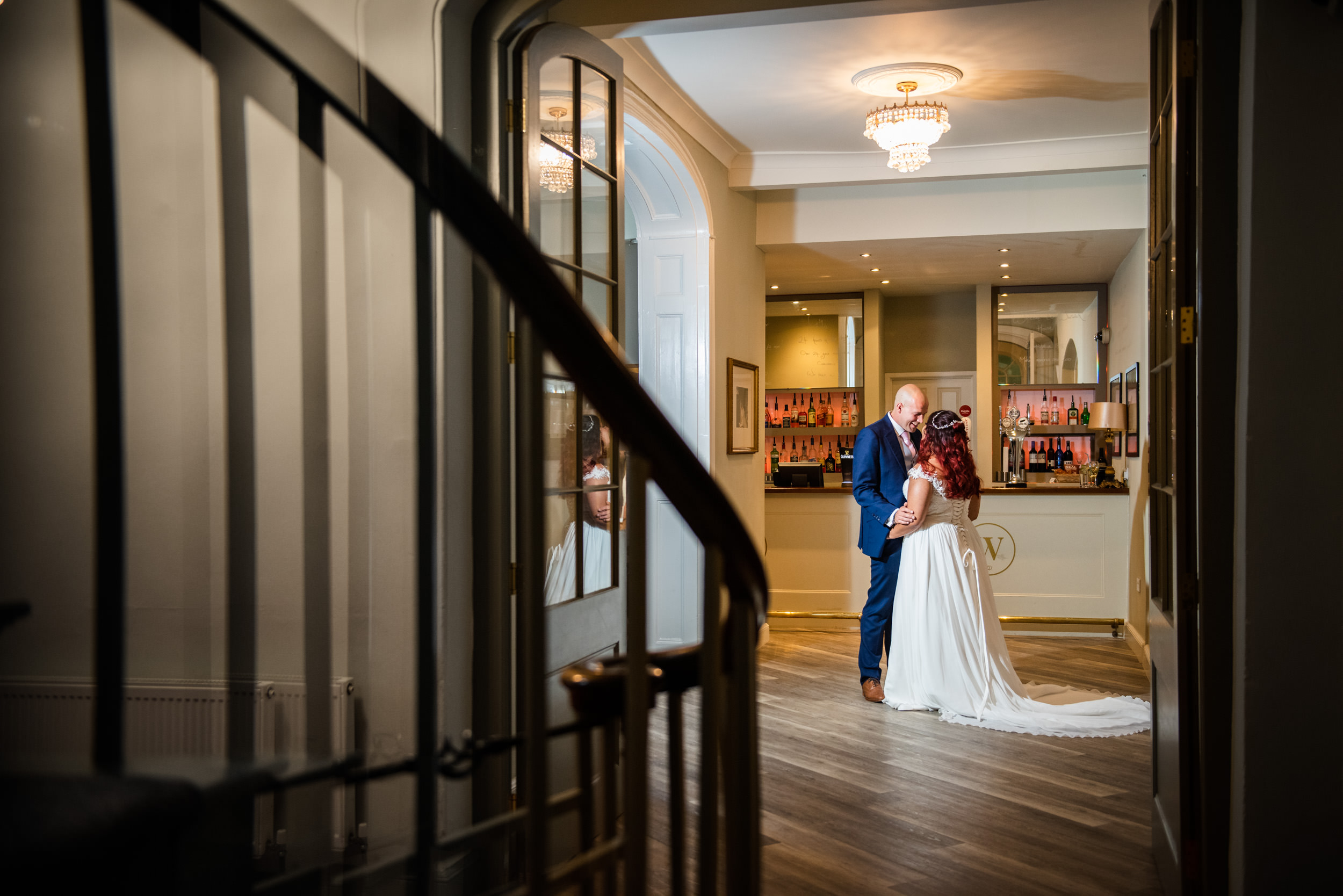 Groom holding his bride and smiling in the lounge bar of Warwick House Wedding Venue