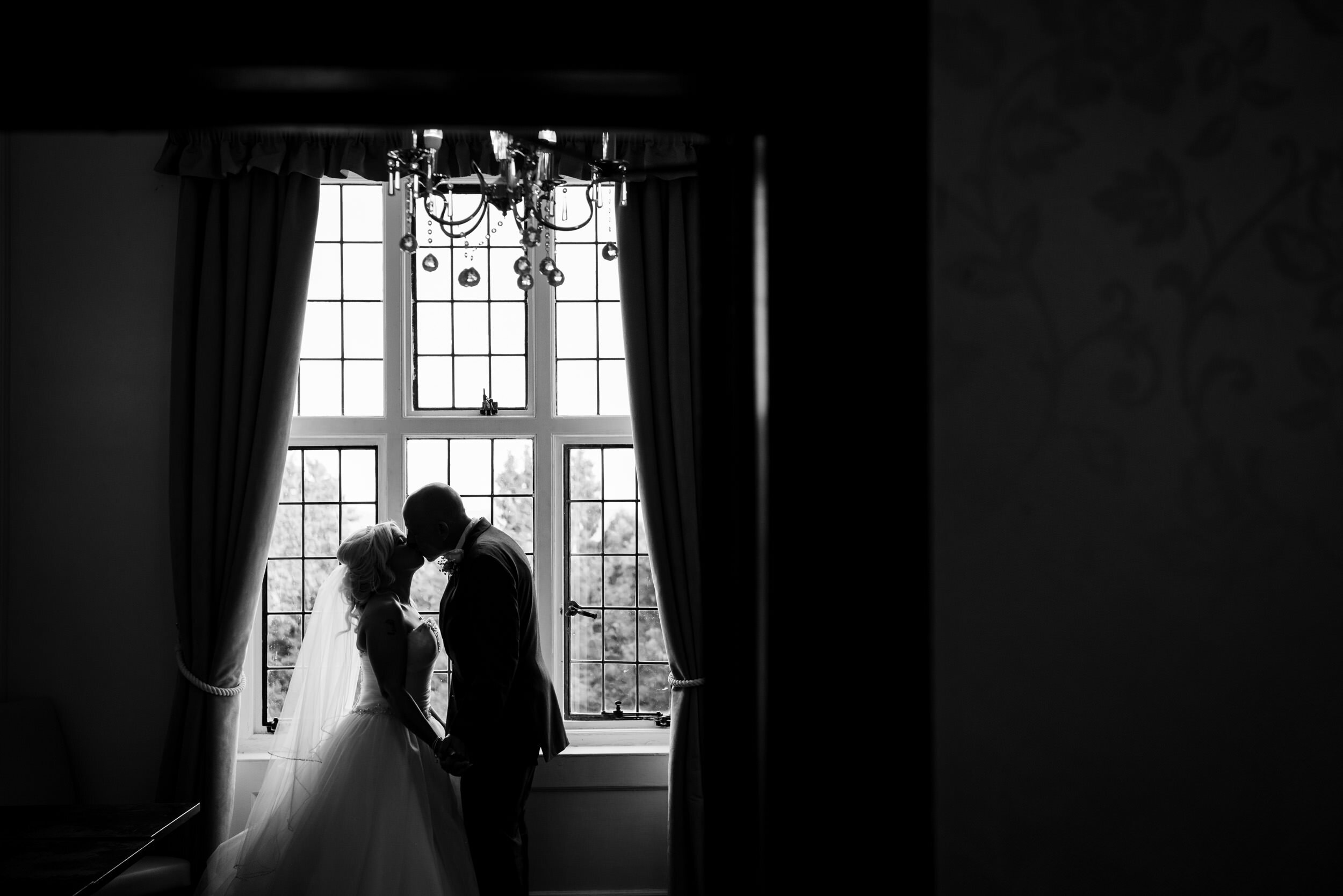 Silhouette image of the Bride and Groom kissing in a bay window at the Southcrest Manor, Redditch