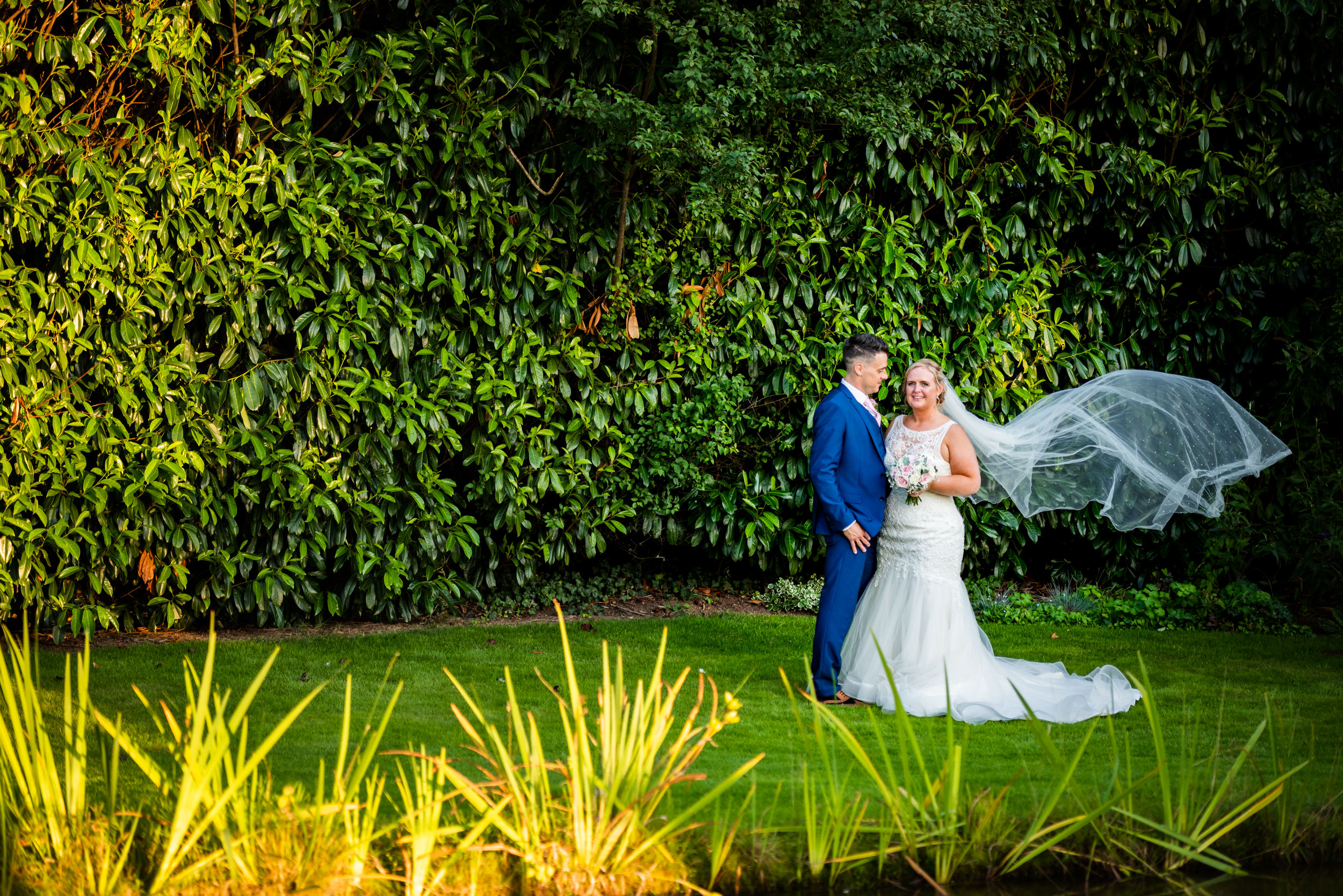 Bride and Groom posing for a photo in the Gardens of Redhouse Barn
