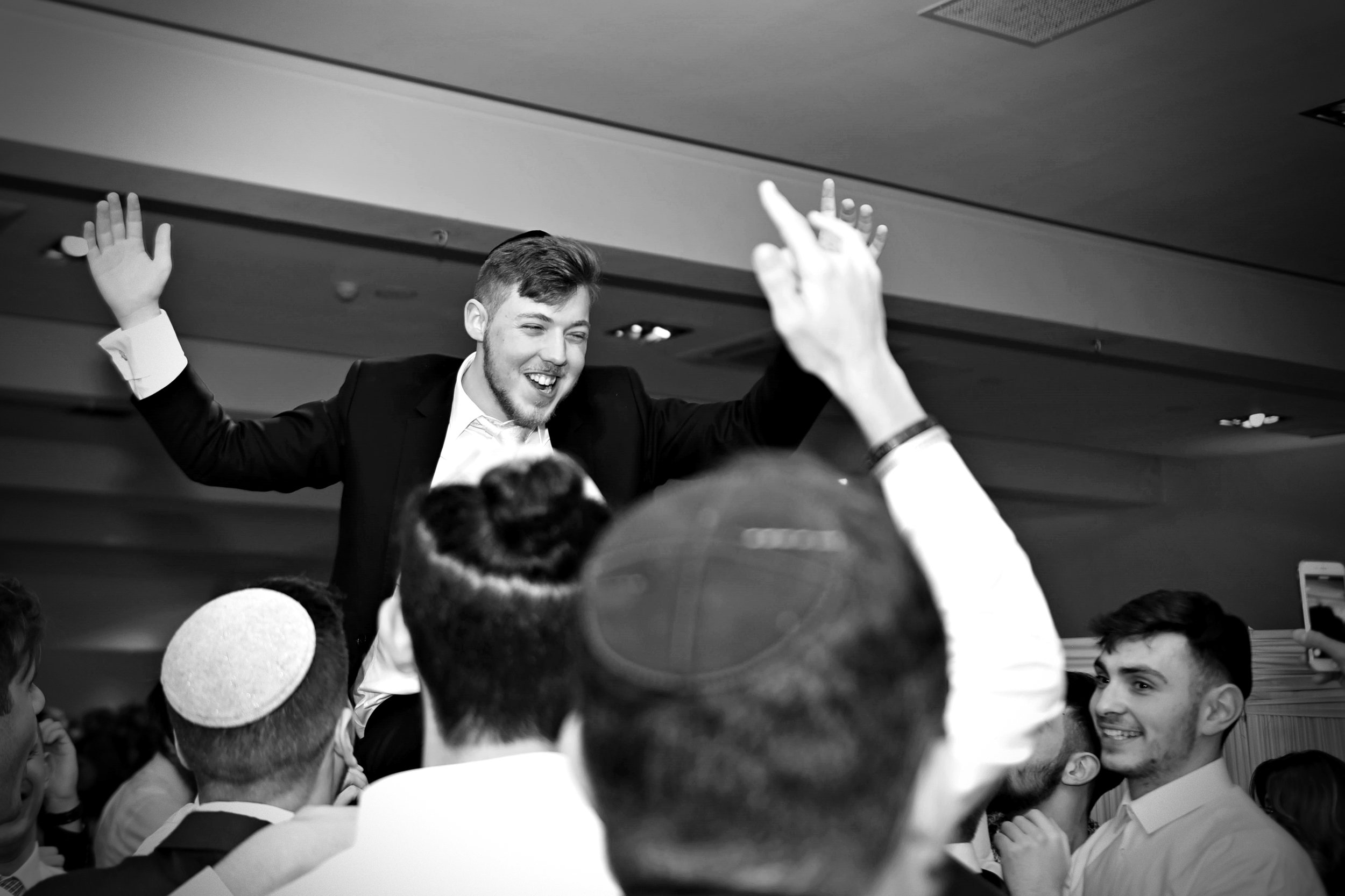 Moshe, the groom, raised onto a friend's shoulders in celebration!