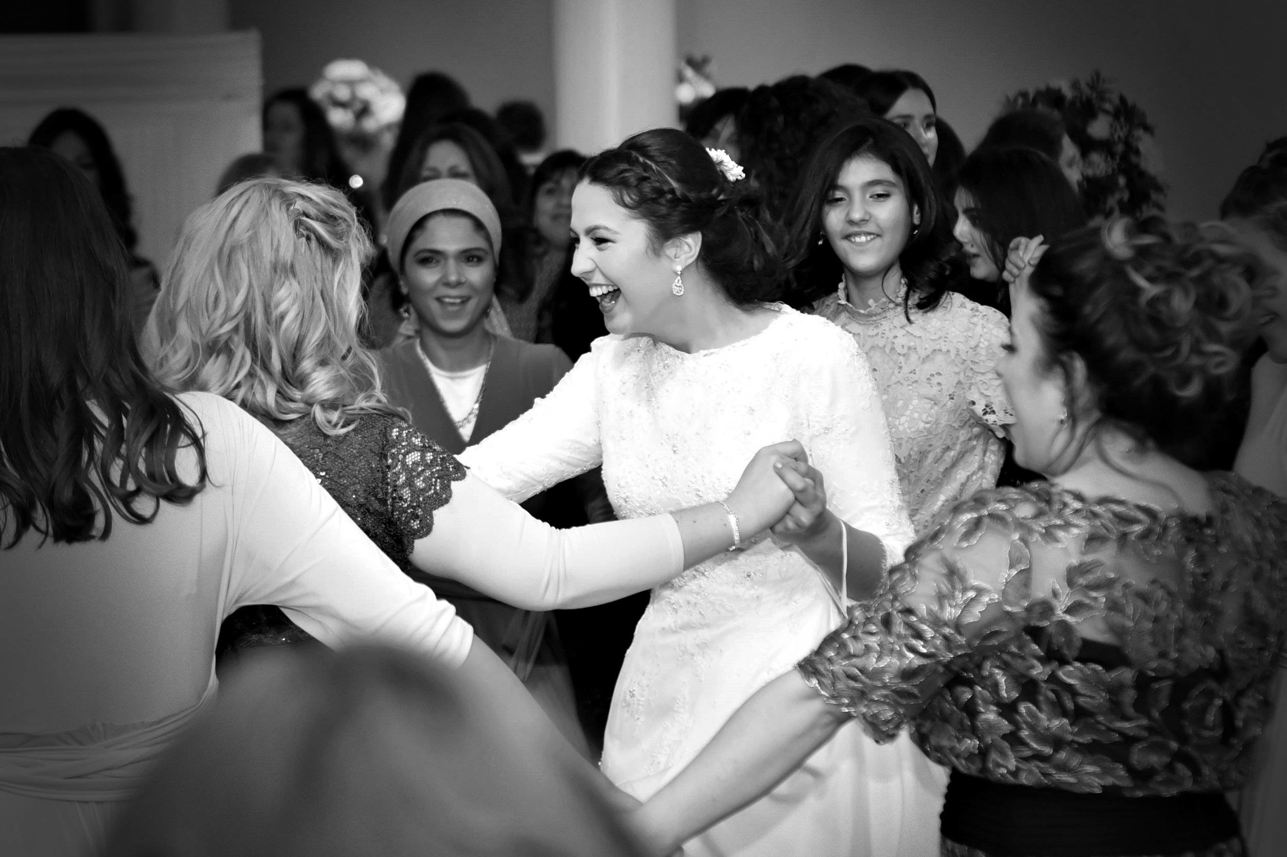 Chava, the bride, dancing with friends and family.