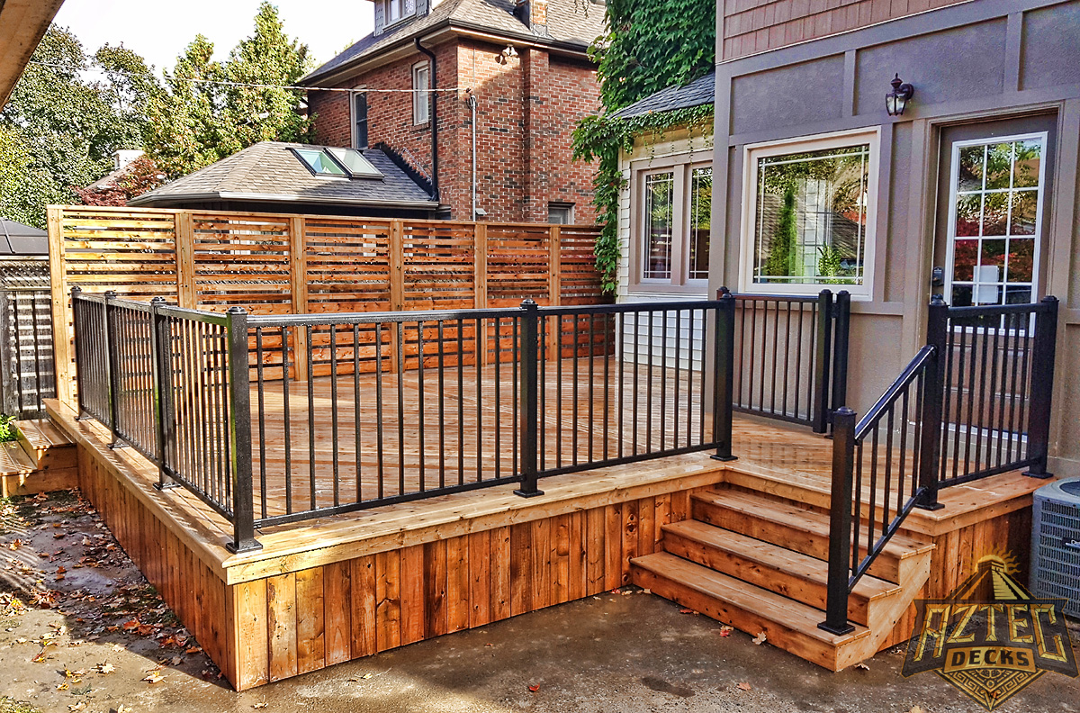 Oshawa deck with privacy wall and aluminum railing built from pressure treated wood