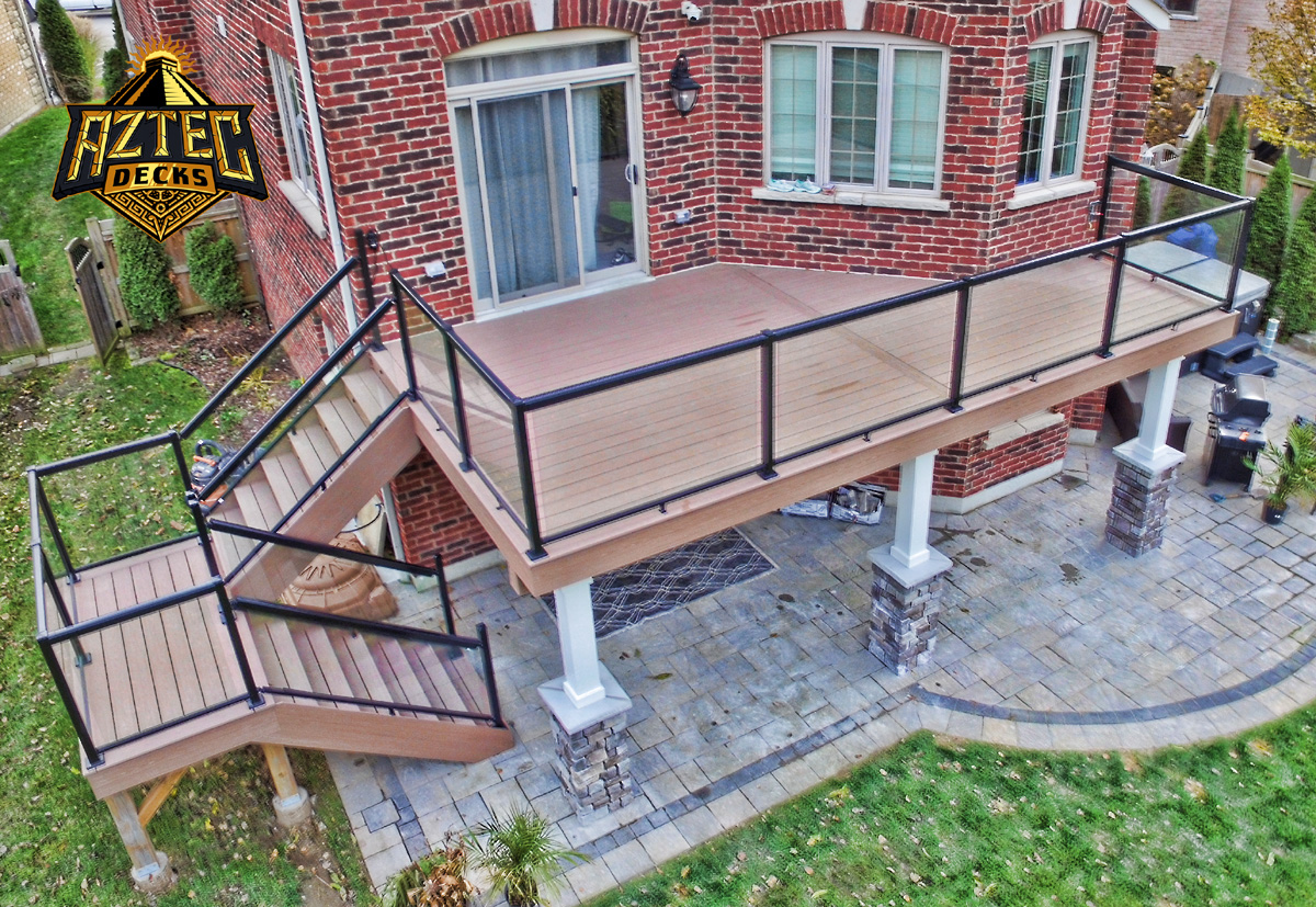 Whitby azek pvc deck with glass railings stone columns and trex rainescape