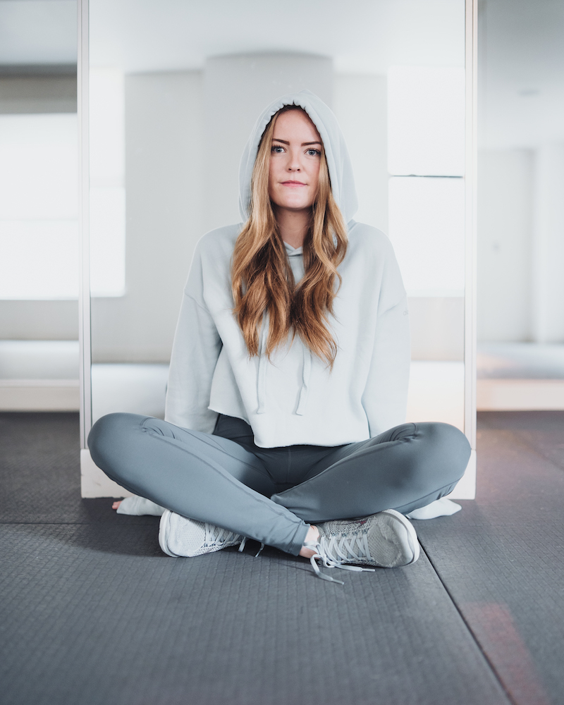 Kaitlyn McMahon of Monika Dixon Public Relations is wearing Lululemon leggings paired with Nike sneakers and Alo Yoga cropped hoodie.