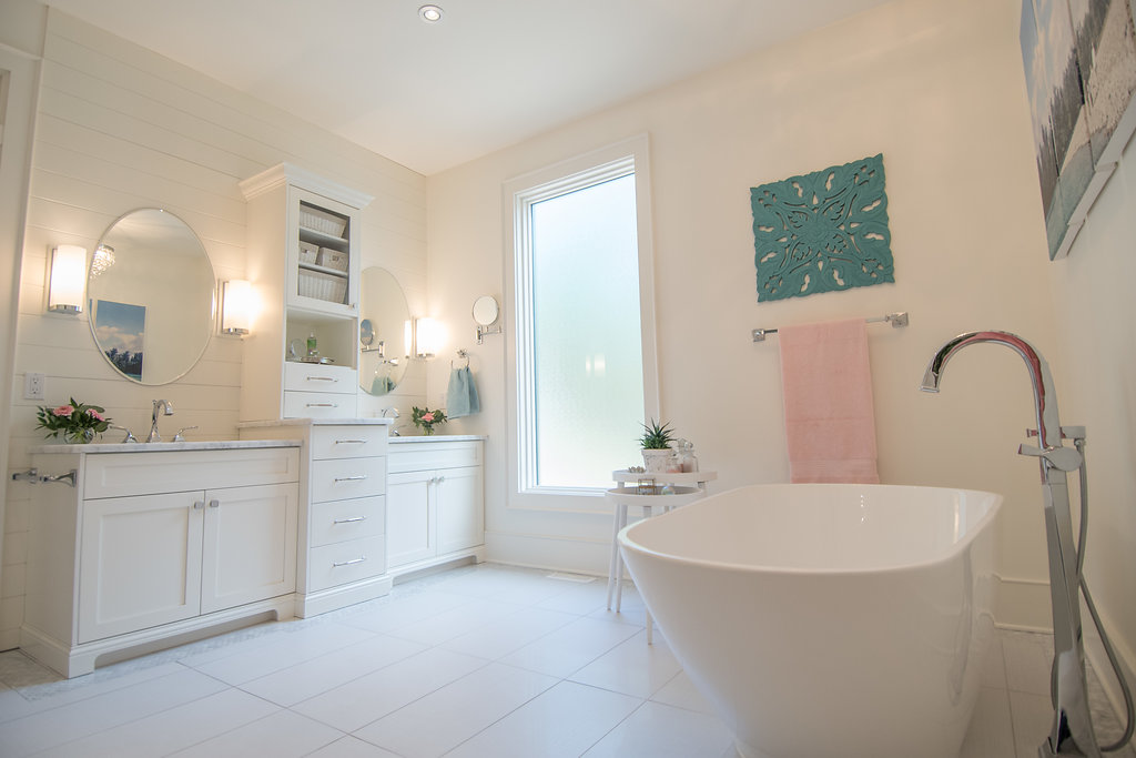 Master Ensuite with freestanding bathtub, sconce lighting, white bathroom vanity with center tower| Interior Designs By Adrienne| Cranbrook BC