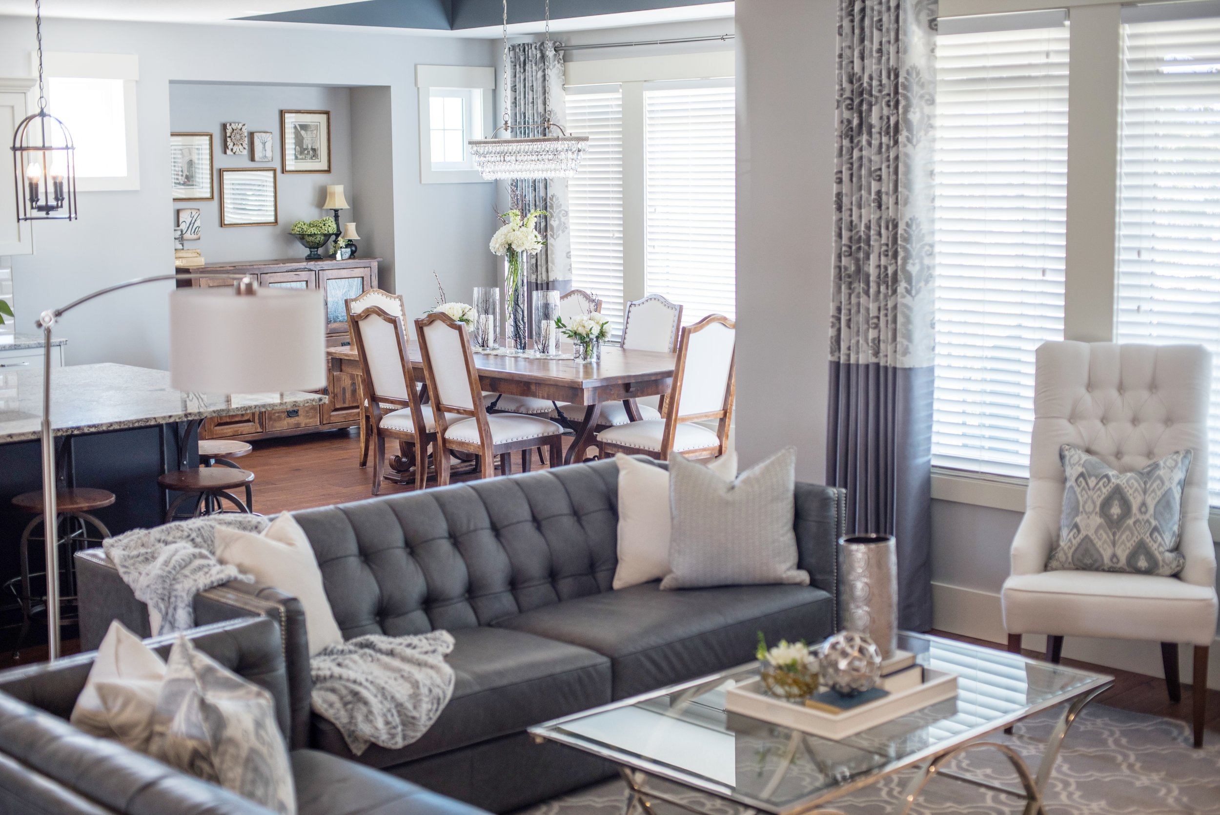 GREY AND WHITE LIVING ROOM, GREY LEATHER FURNITURE, GLASS COFFEE TABLE, WHITE UPHOLSTERED CHAIR, DRAPERY, INTERIOR DESIGNS BY ADRIENNE, CRANBROOK BC