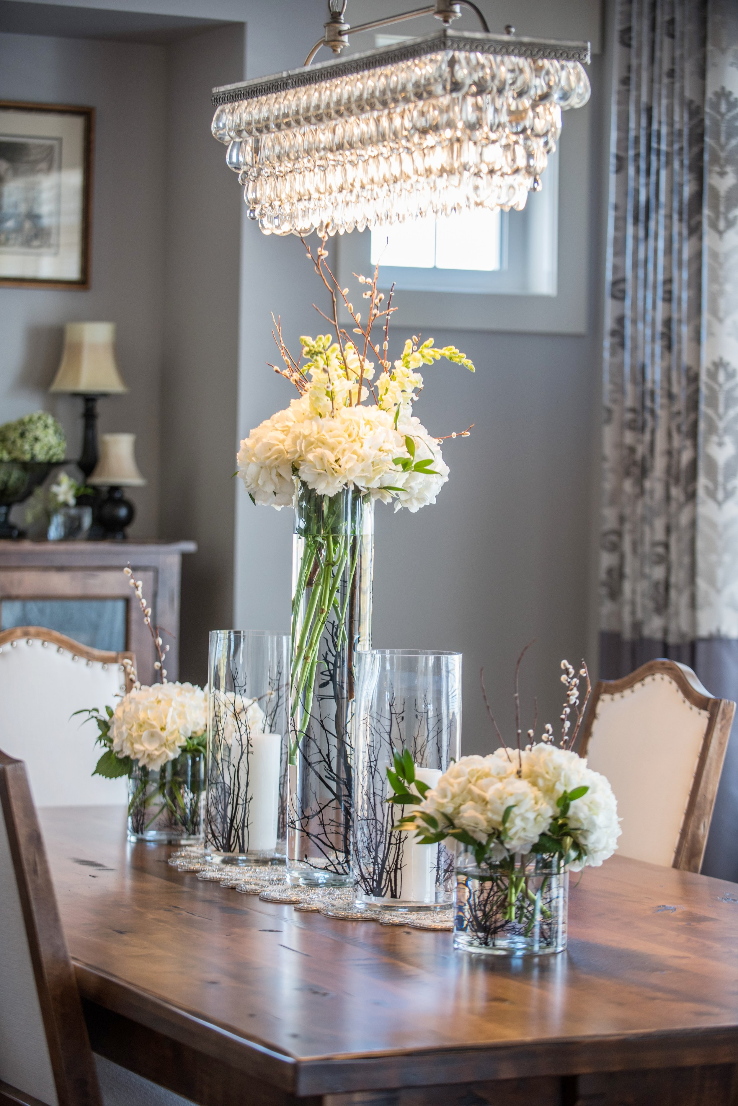 Dining room with white upholstered chairs and farmhouse table. Pottery barn rectangular chandelier, Interior Designs By Adrienne, Cranbrook BC